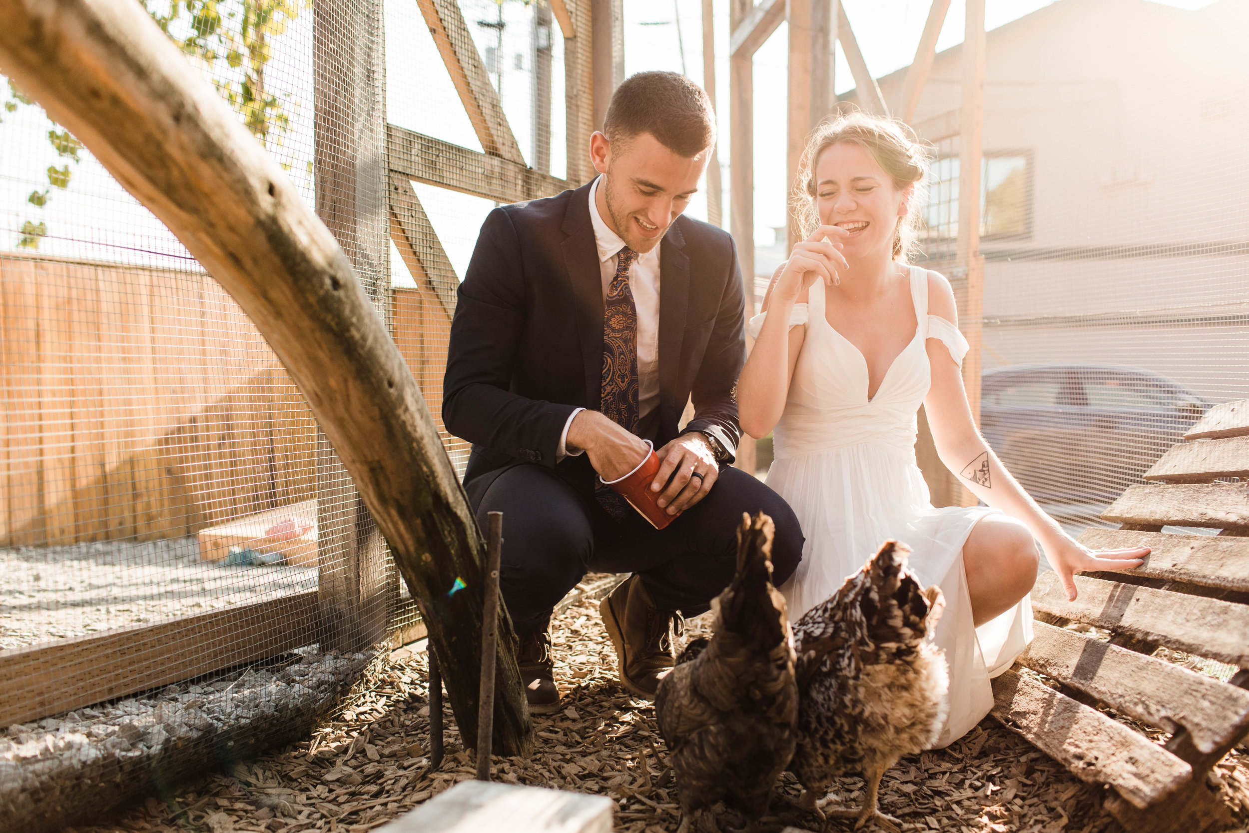 couple feeding the chickens at Humble Pie in Seattle Washington after their Mt Rainier elopement | Seattle Washington adventure wedding photographers