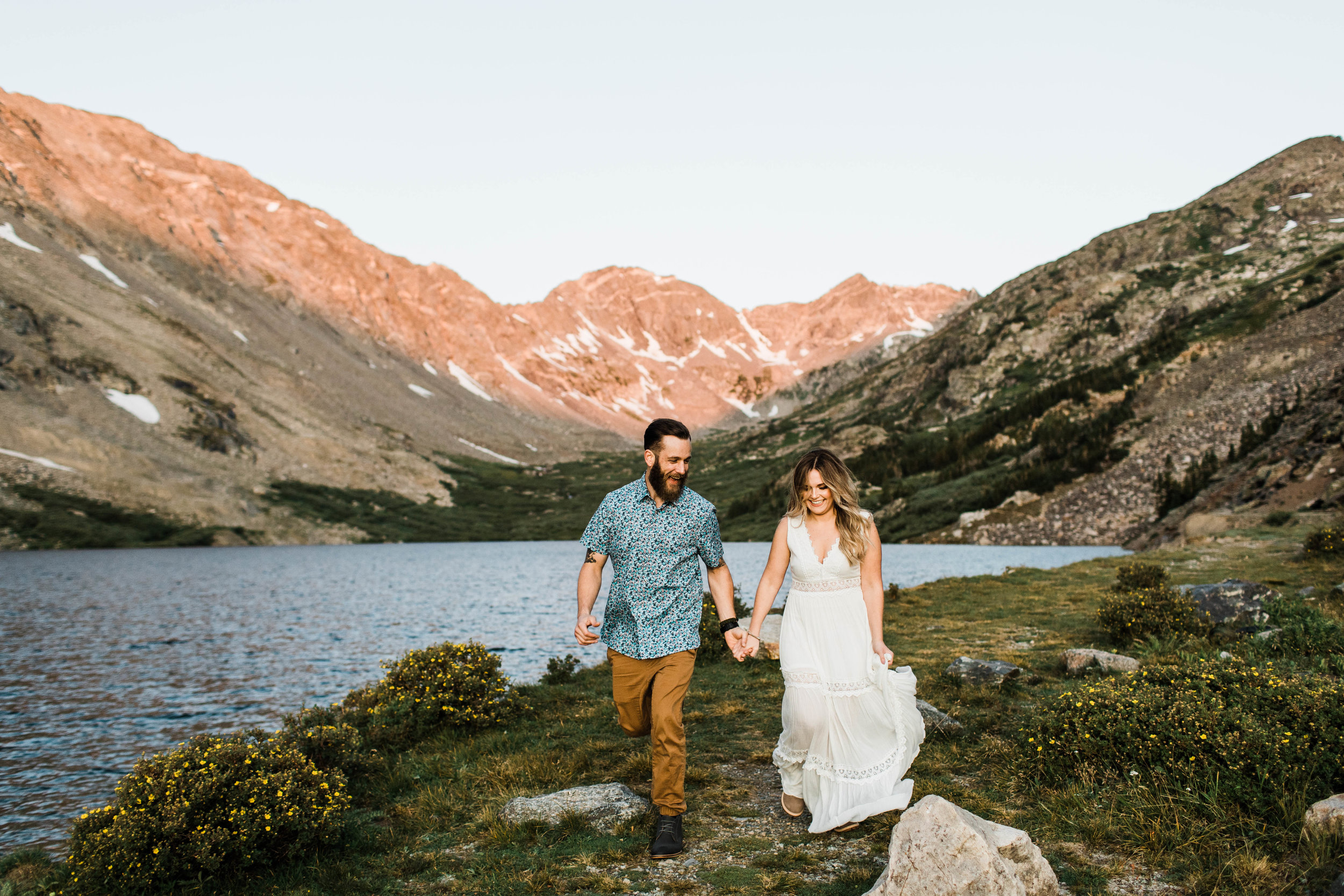 Engaged couple running together in the mountains during their Breckenridge adventure engagement photos at an alpine lake | Breckenridge elopement and adventure wedding photographers