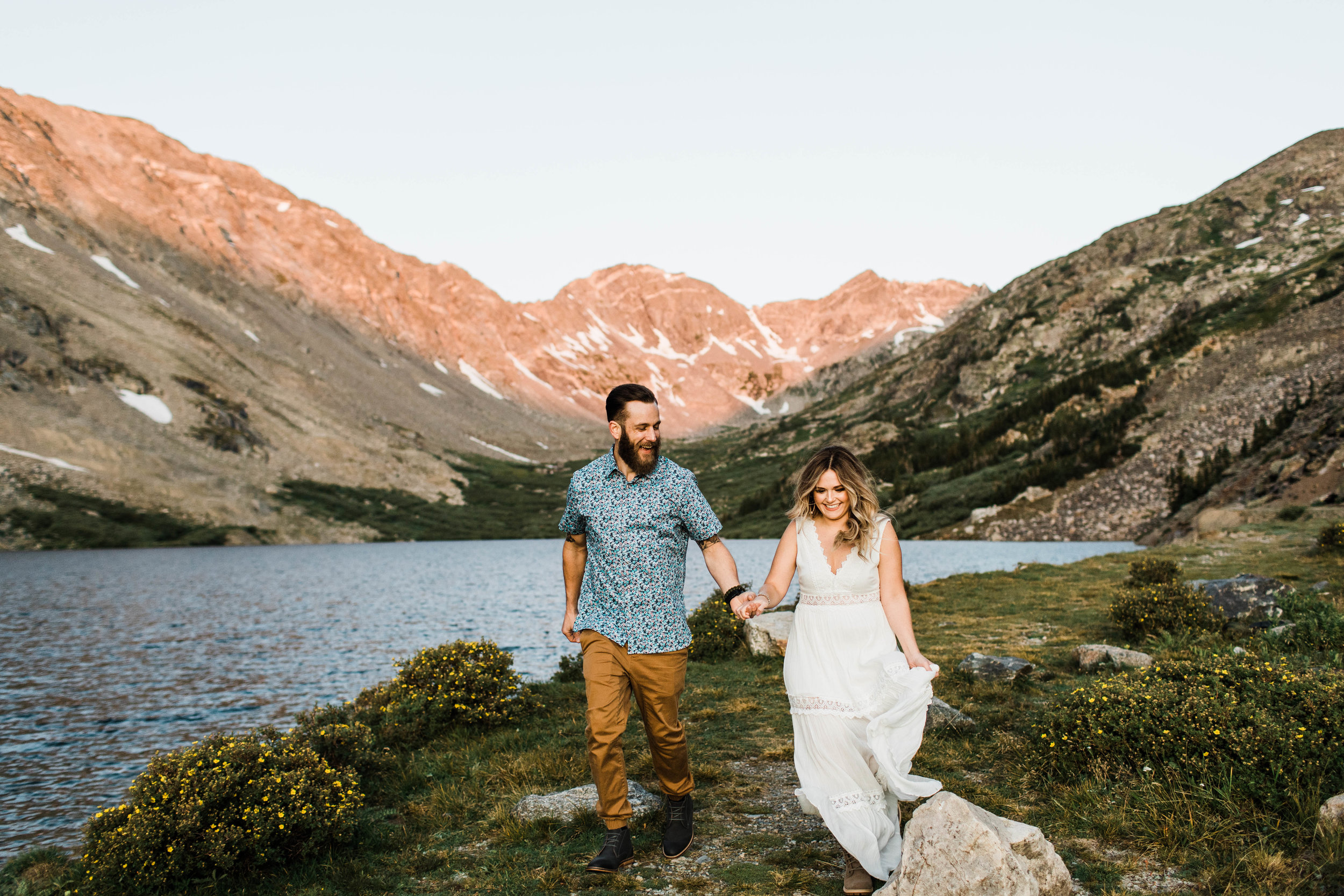 Engaged couple running together in the mountains during their Breckenridge adventure engagement photos at an alpine lake | best Breckenridge elopement and adventure wedding photographers