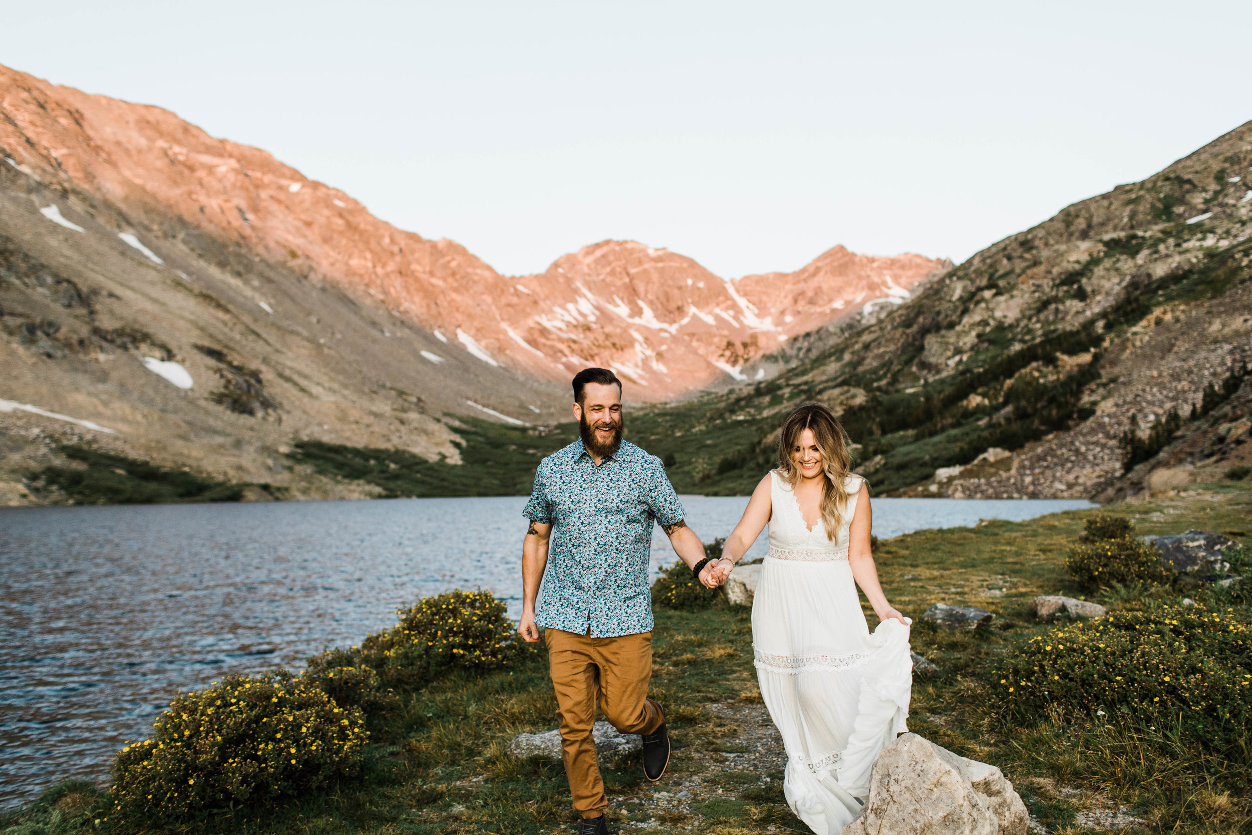 Engaged couple running together in the mountains during their Breckenridge adventure engagement photos at an alpine lake | Breckenridge CO elopement  and wedding photographers