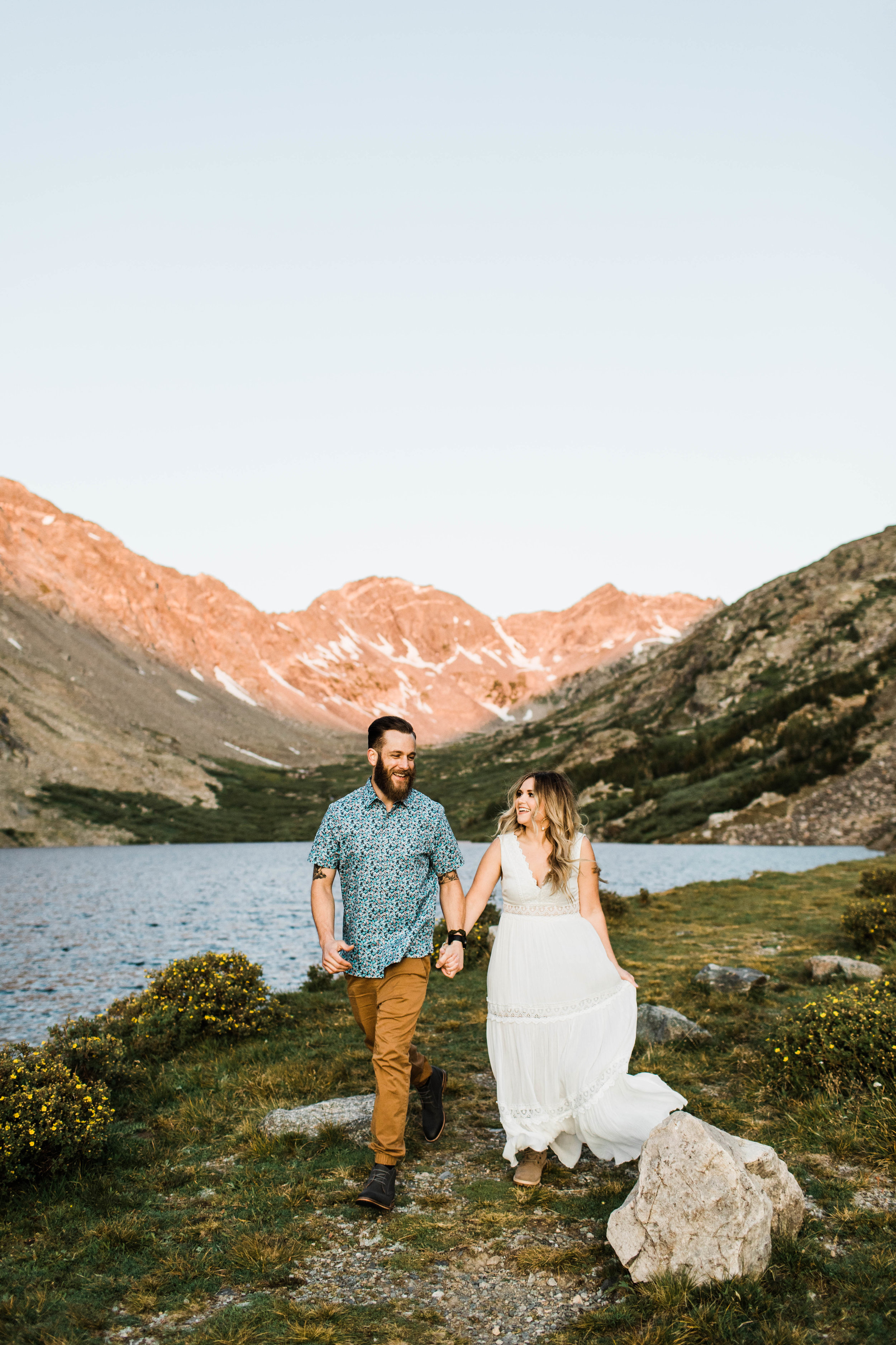 Engaged couple running together in the mountains during their Breckenridge adventure engagement photos at an alpine lake | best Breckenridge Colorado wedding and elopement photographers