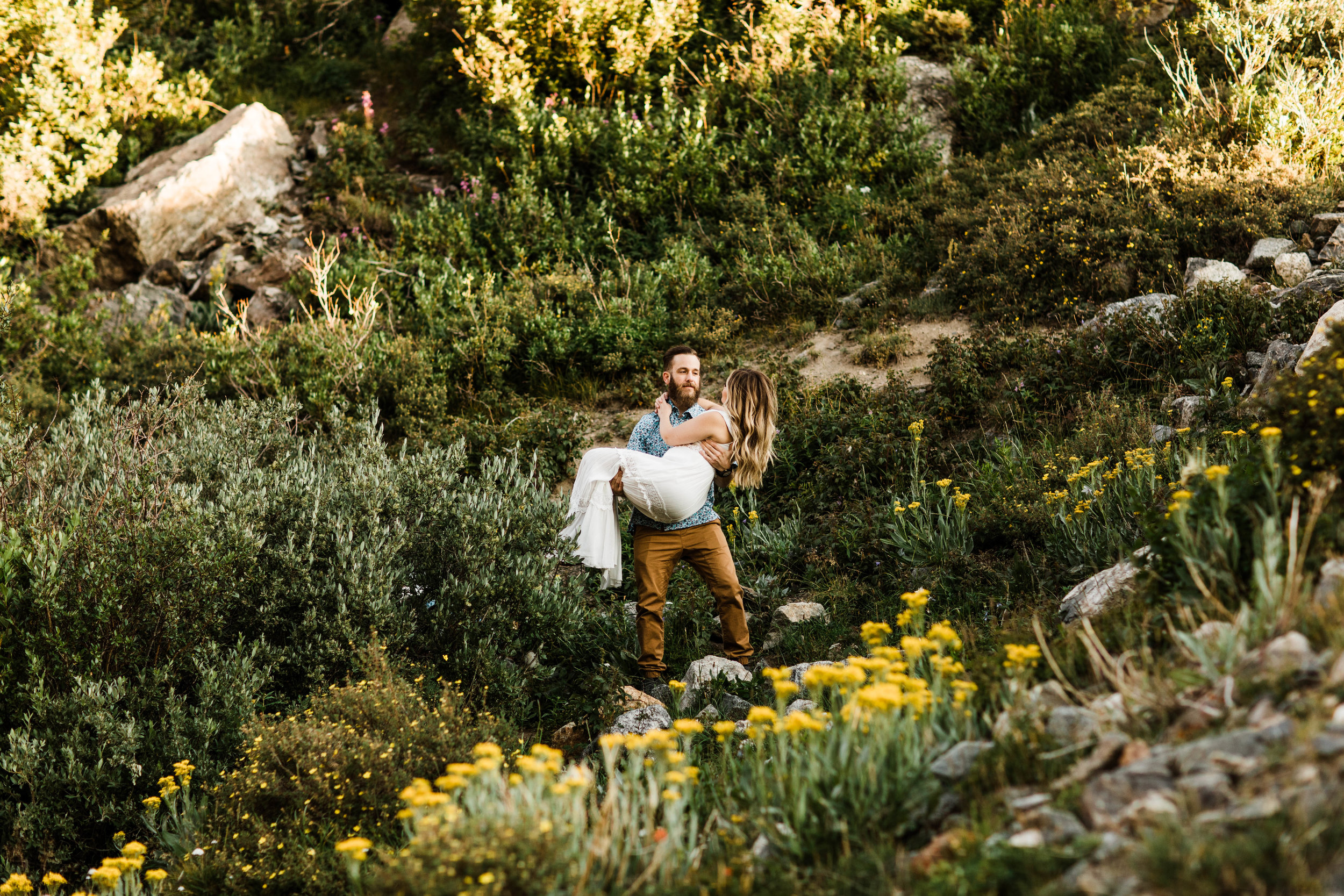 groom holding bride in a mountain wildflower meadow during elopement style photos in Colorado | Breckenridge wedding and adventure elopement photographers