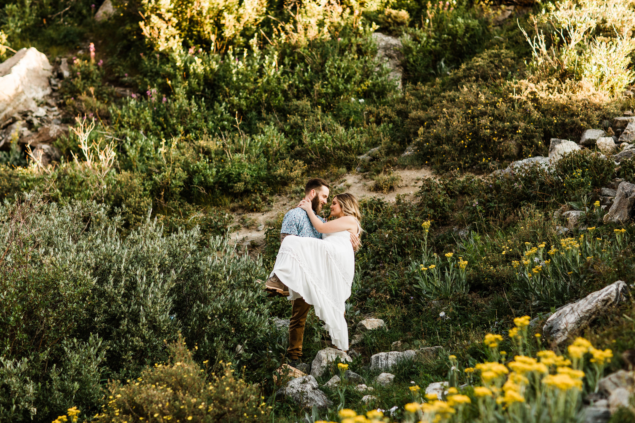 groom holding bride in a mountain wildflower meadow during elopement style photos in Colorado | Breckenridge CO wedding and elopement photographers
