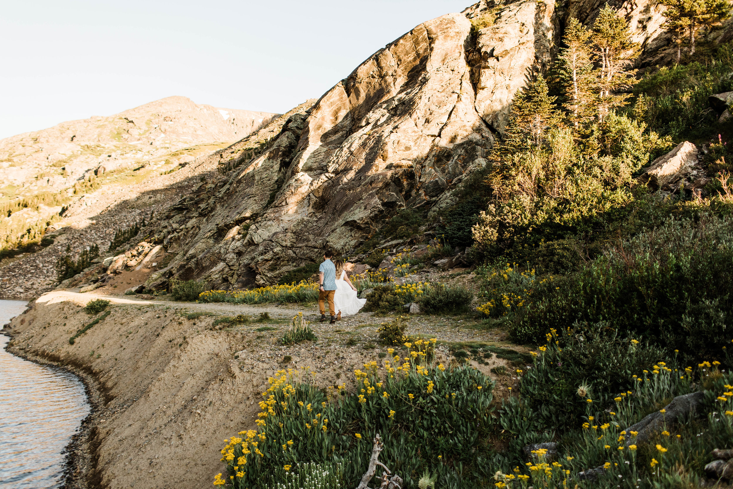 eloping couple running through a meadow of mountain wildflowers while holding hands | Breckenridge Colorado wedding photographers