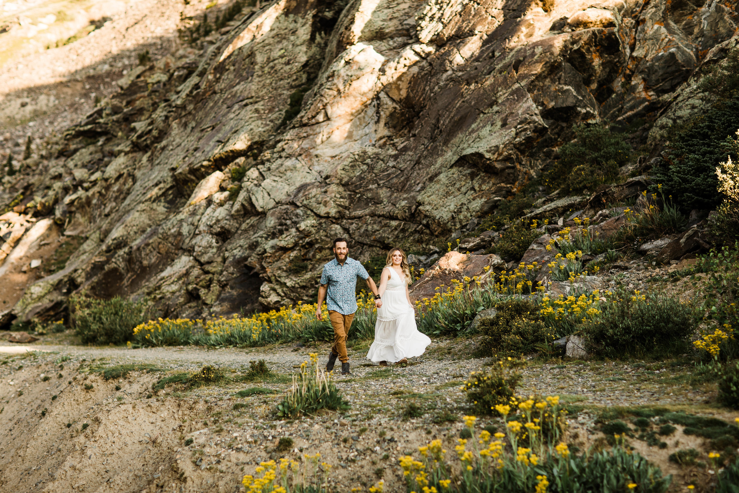 eloping couple running through a meadow of mountain wildflowers while holding hands | Breckenridge adventure wedding photographers