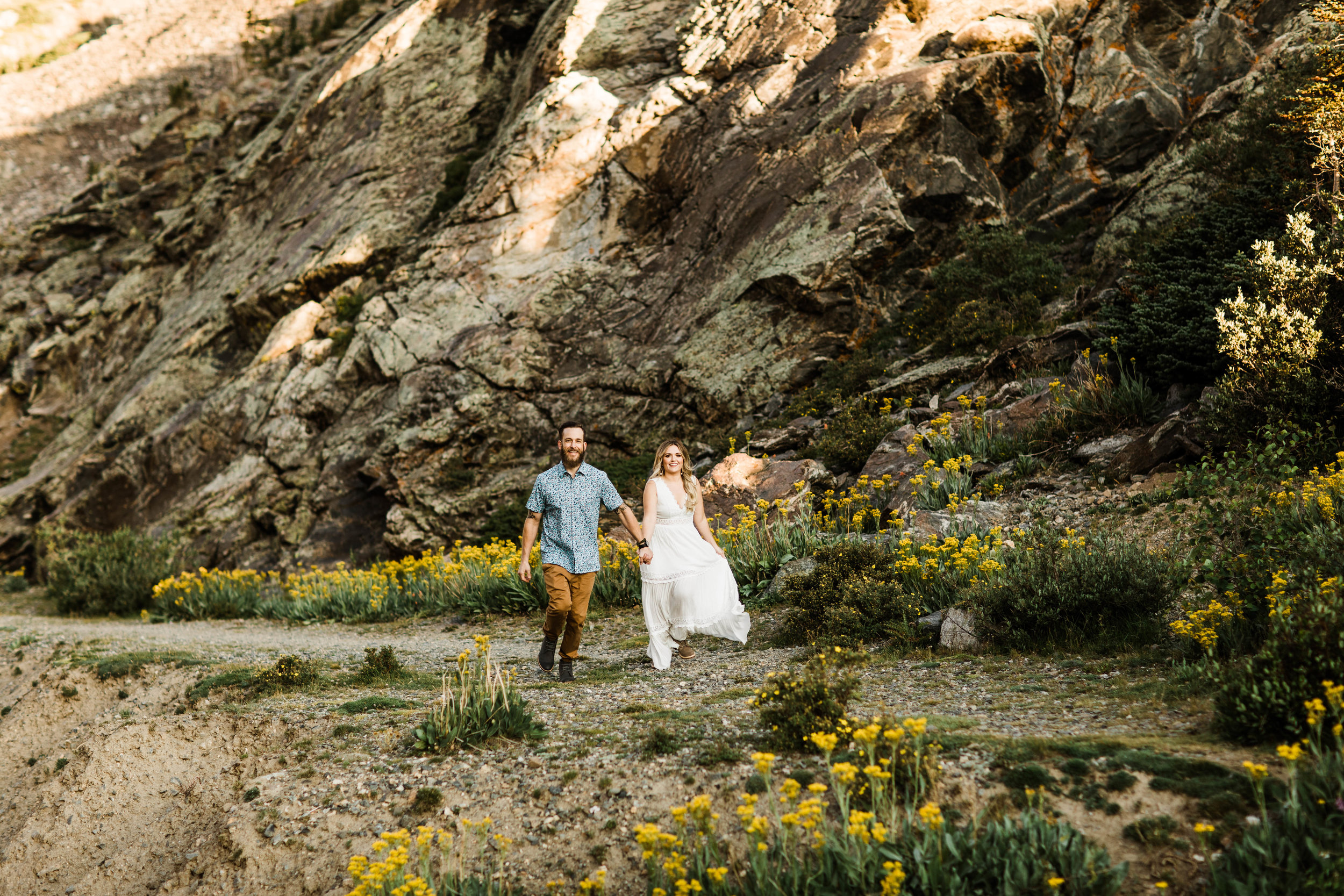 eloping couple running through a meadow of mountain wildflowers while holding hands | Breckenridge mountain wedding photographers