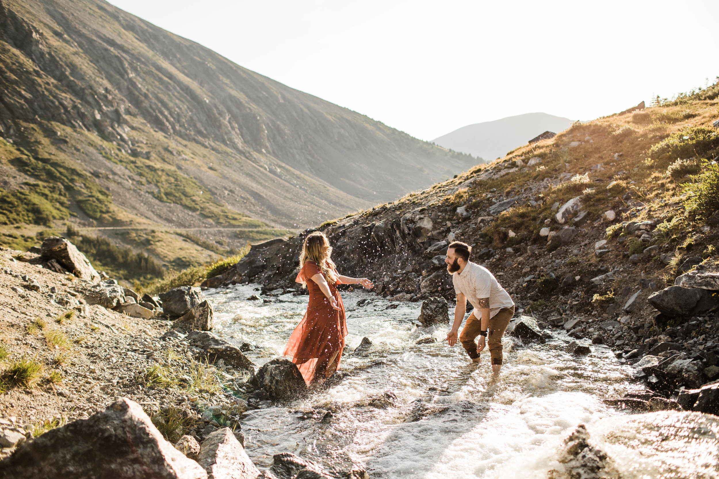 eloping couple splashing around in a creek during their adventurous engagement photos in the mountains of Colorado | Breckenridge adventure wedding photographers