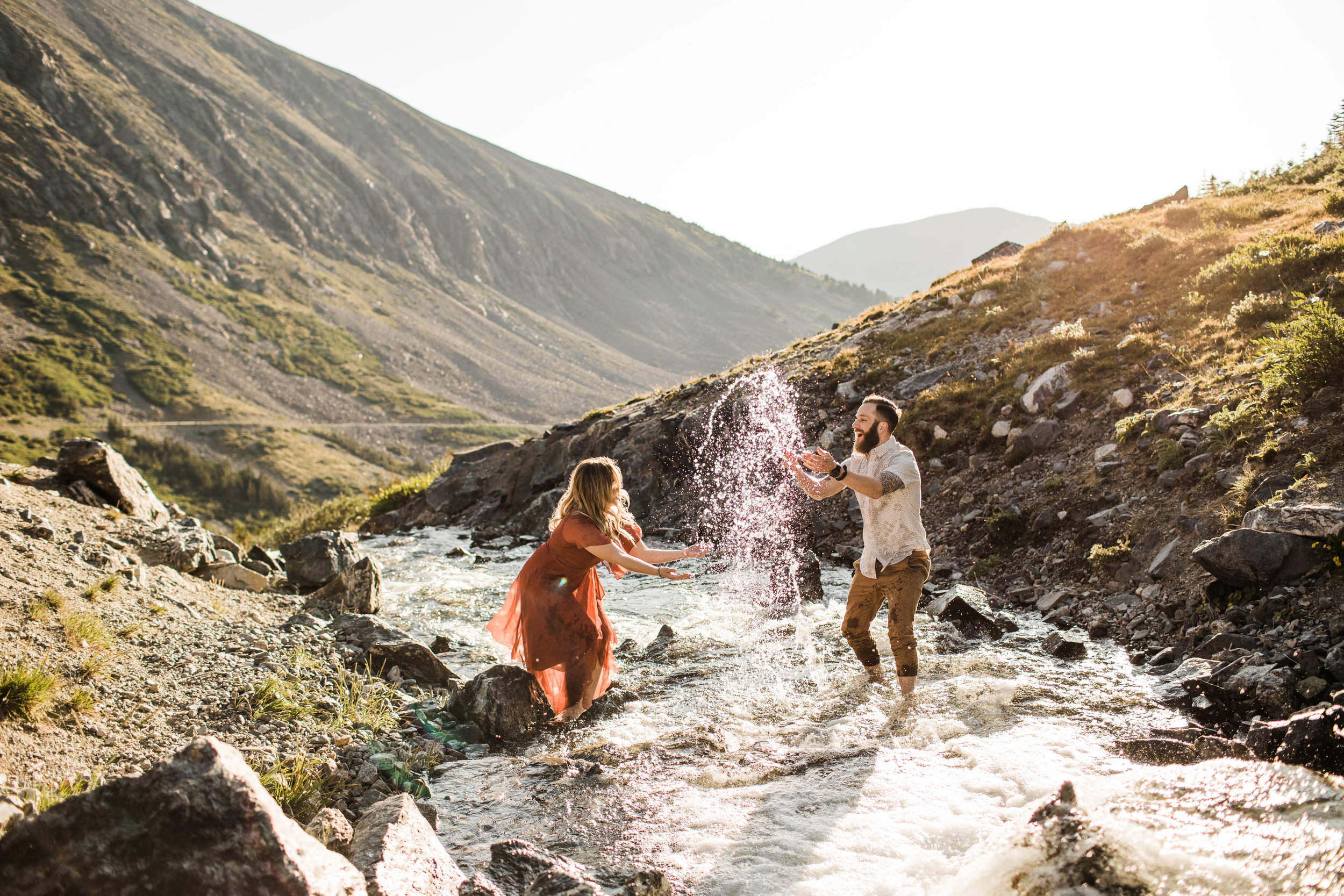 eloping couple splashing around in a creek during their adventurous engagement photos in the mountains of Colorado | Breckenridge wedding and elopement photographers