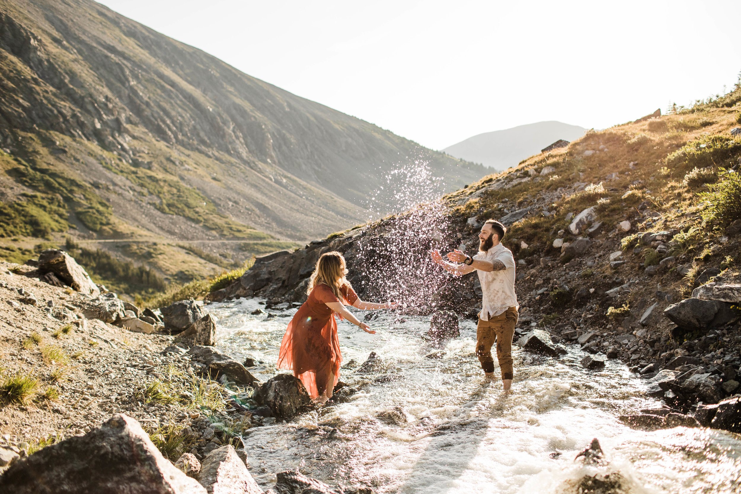 eloping couple splashing around in a creek during their adventurous engagement photos in the mountains of Colorado | Breckenridge Colorado wedding photographers