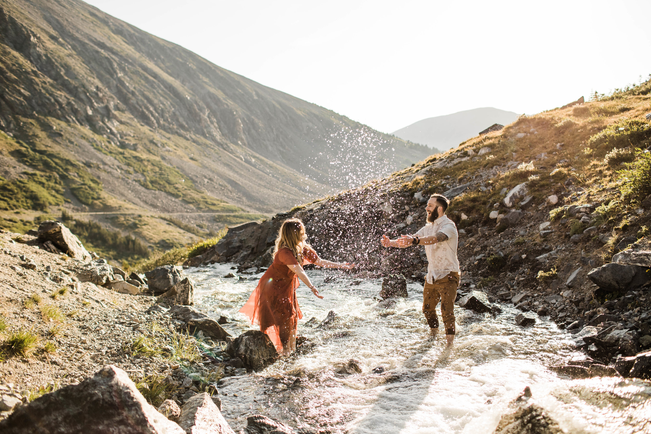 eloping couple splashing around in a creek during their adventurous engagement photos in the mountains of Colorado | Breckenridge small adventure wedding photographers