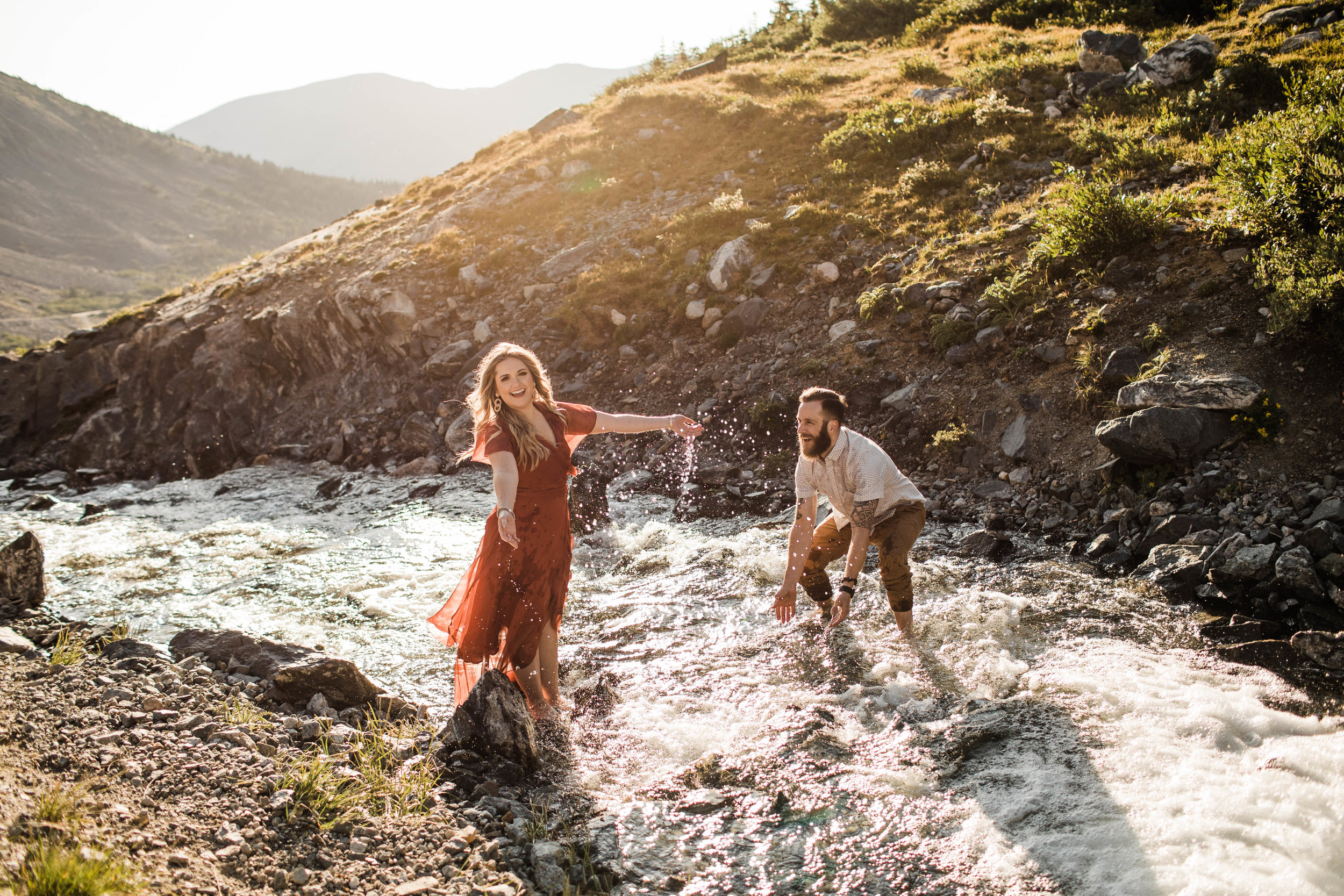 eloping couple splashing around in a creek during their adventurous engagement photos in the mountains of Colorado | Breckenridge elopement photographers