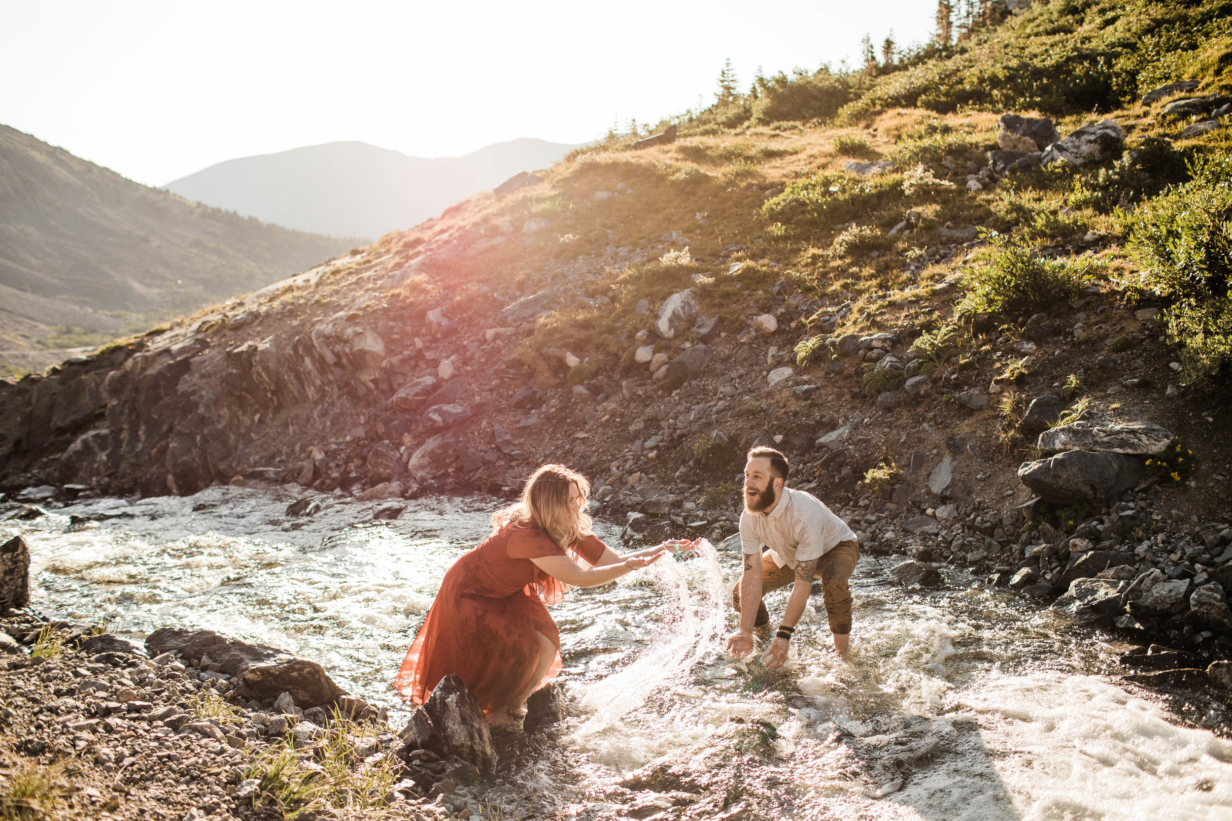 eloping couple splashing around in a creek during their adventurous engagement photos in the mountains of Colorado | Breckenridge adventure elopement photographers