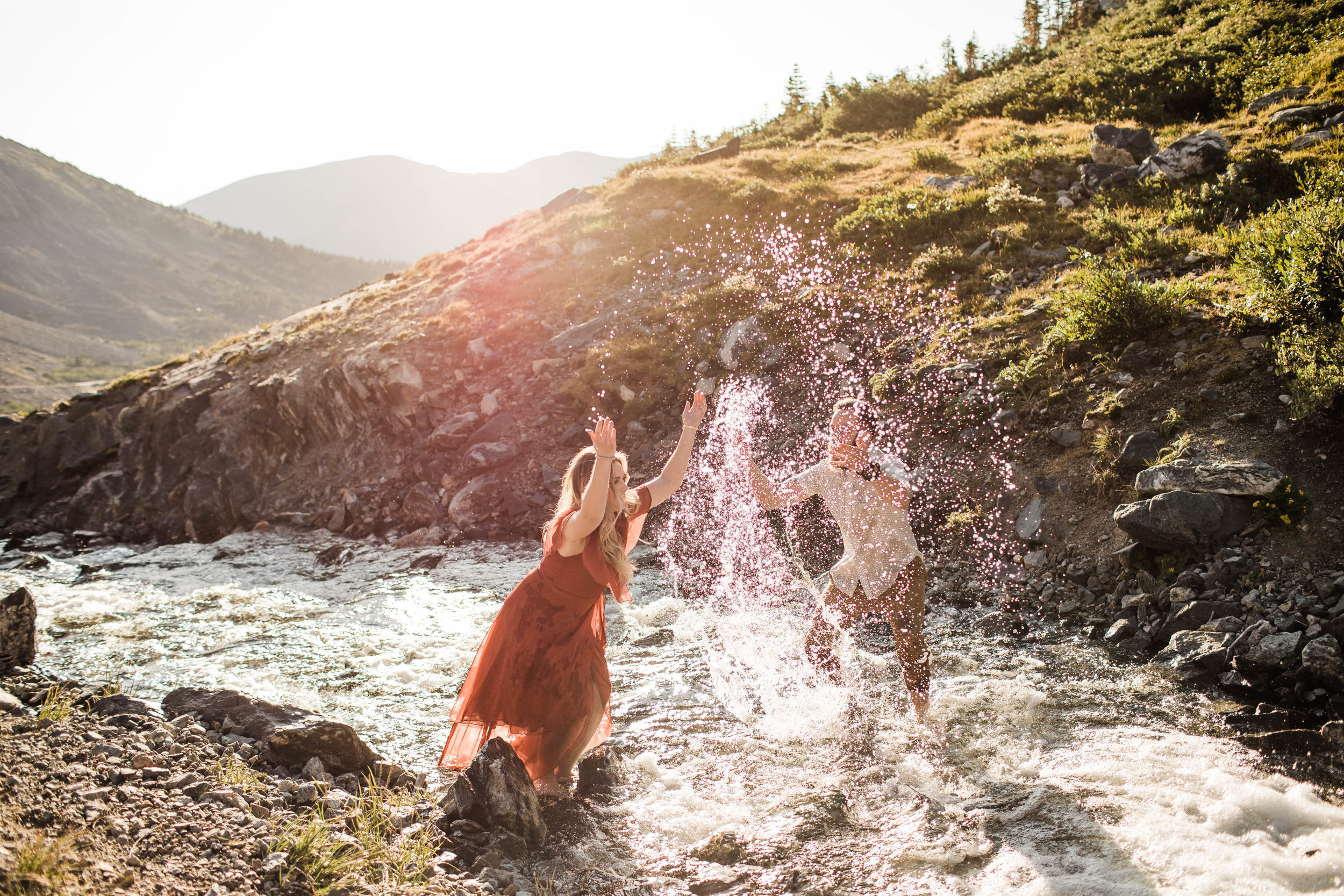 eloping couple splashing around in a creek during their adventurous engagement photos in the mountains of Colorado | Breckenridge adventure weddings and elopements