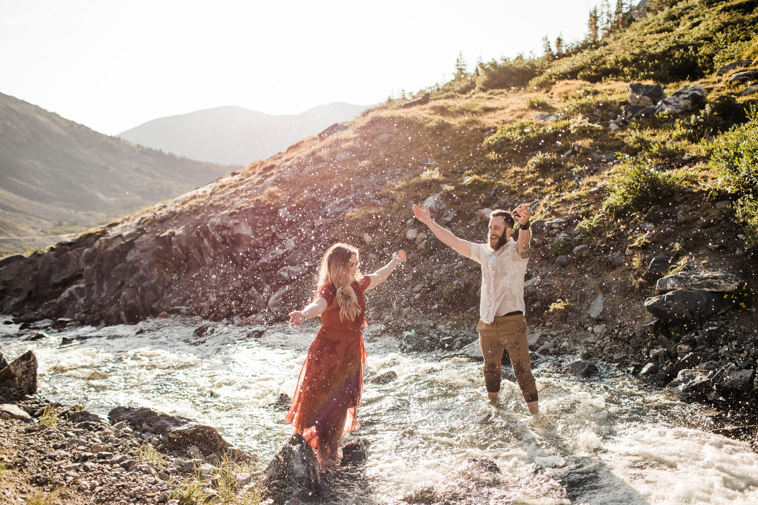 eloping couple splashing around in a creek during their adventurous engagement photos in the mountains of Colorado | Breckenridge adventure elopements