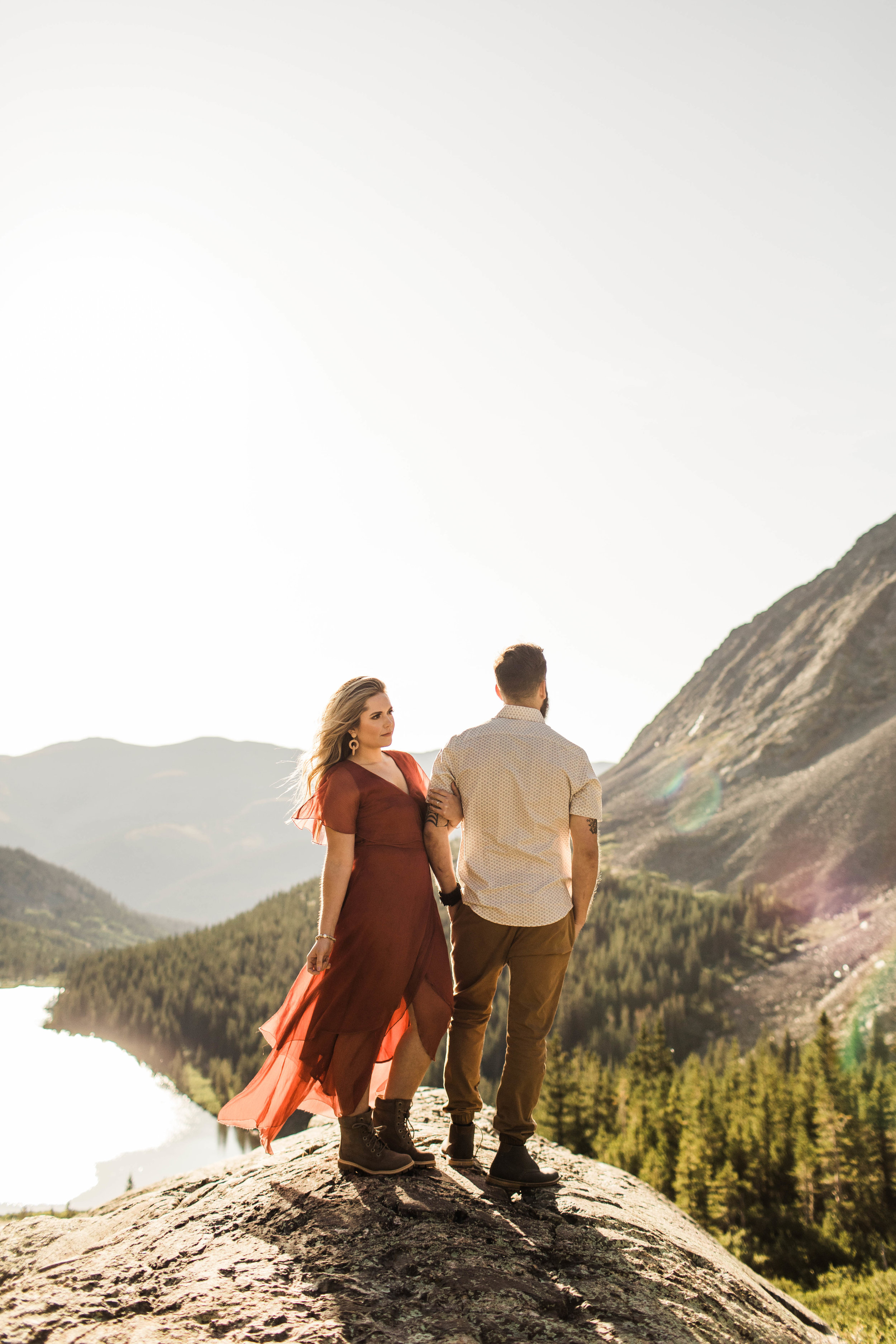 couple standing on the edge of a mountain during their Breckenridge pre-wedding adventure engagement photos