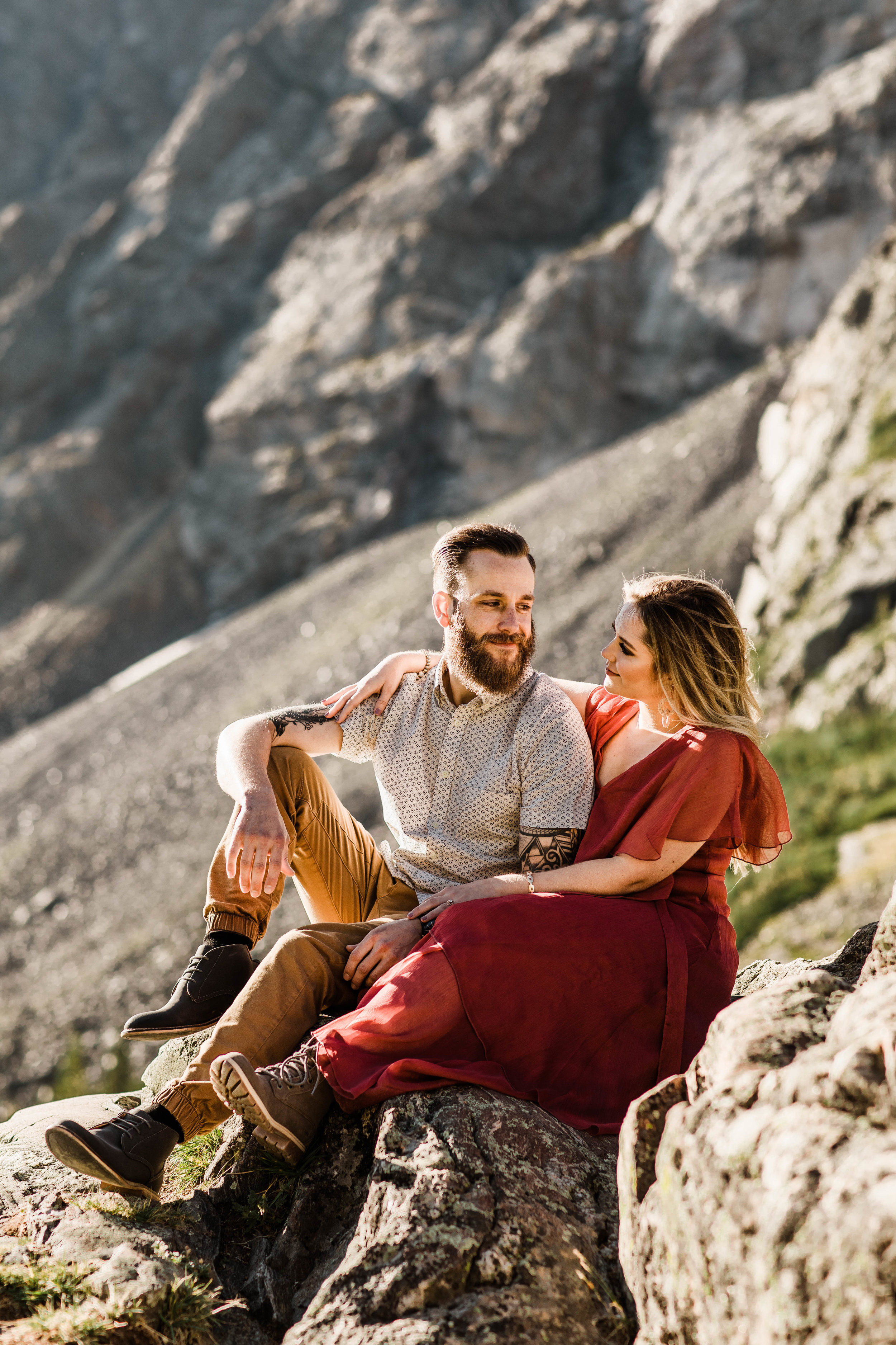 couple eloping in Breckenridge sitting on the edge of a mountain for adventurous engagement photos before their Colorado adventure elopement