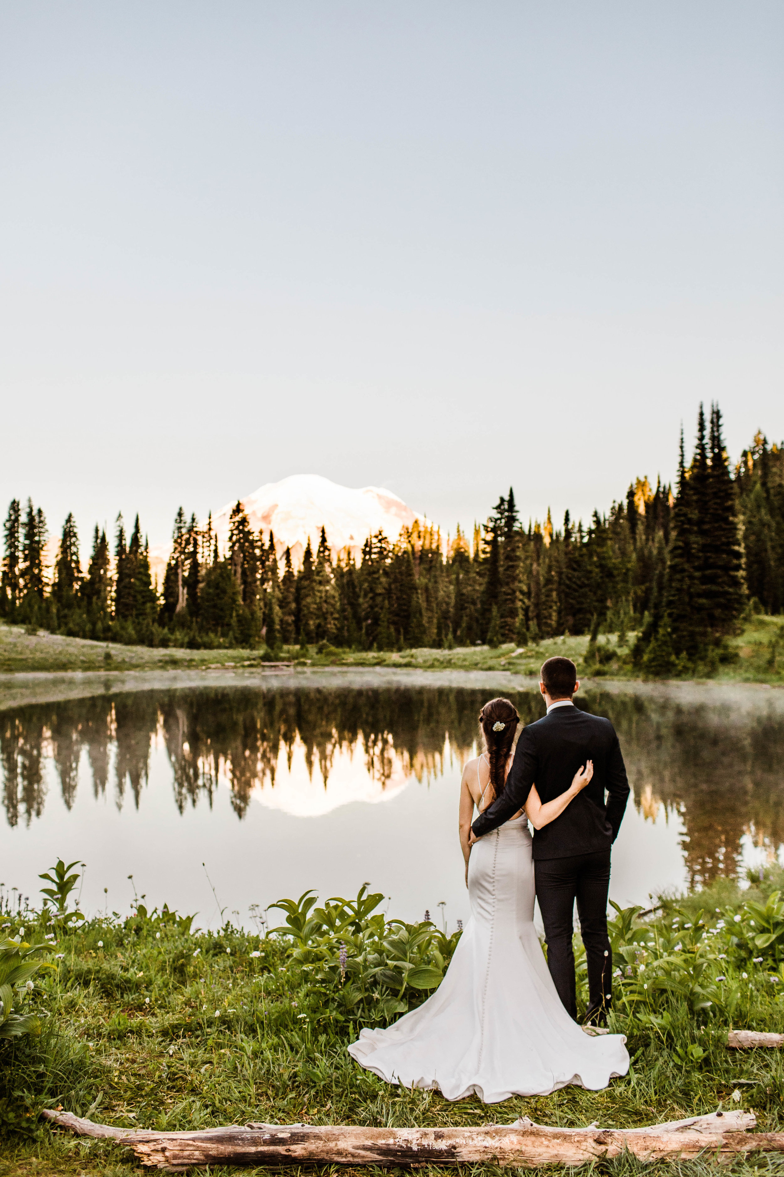 eloping couple standing by an alpine lake during their Mount Rainier National Park elopement | Washington adventure wedding photographers