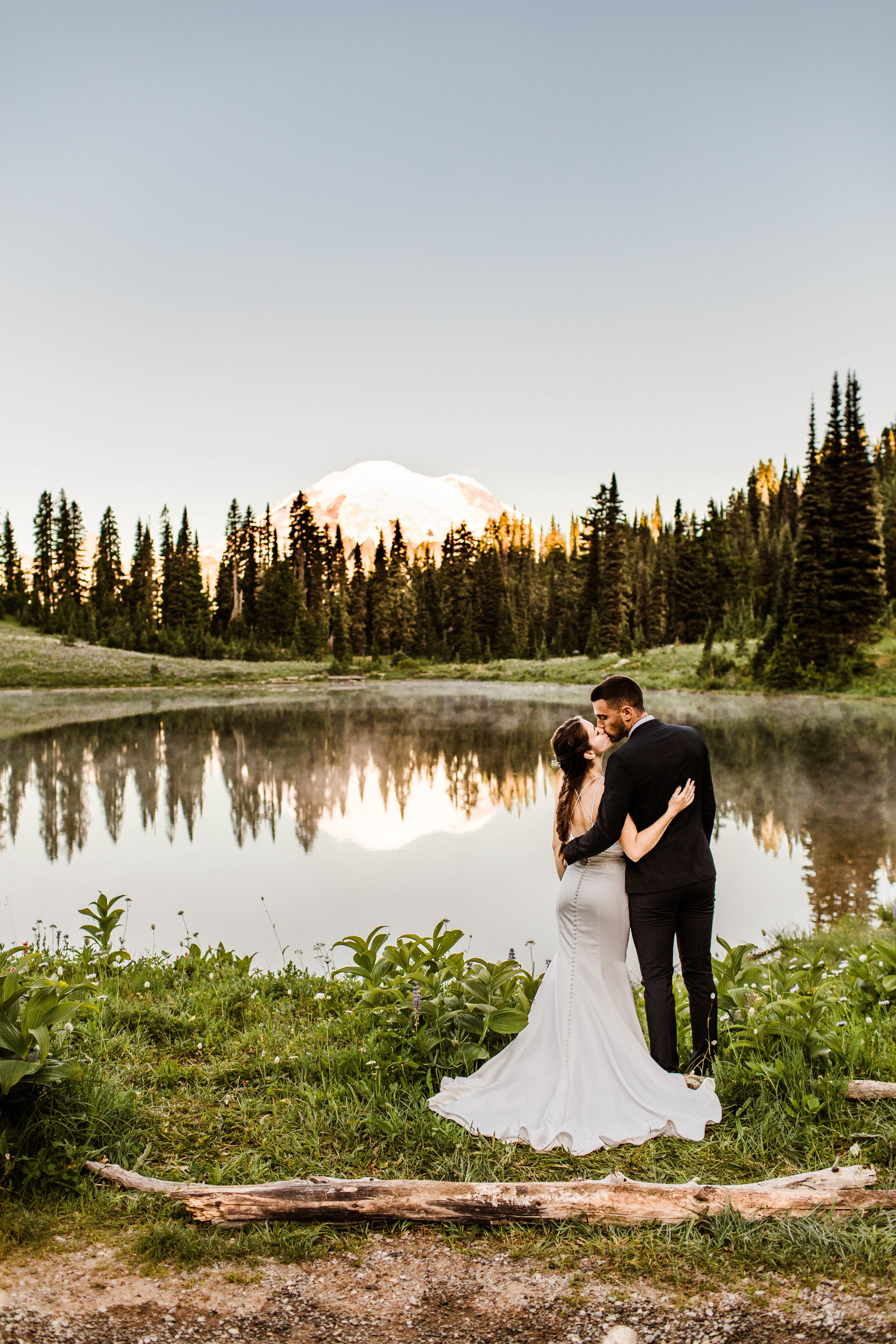 eloping couple standing by an alpine lake during their Mount Rainier National Park elopement | Washington adventure weddings