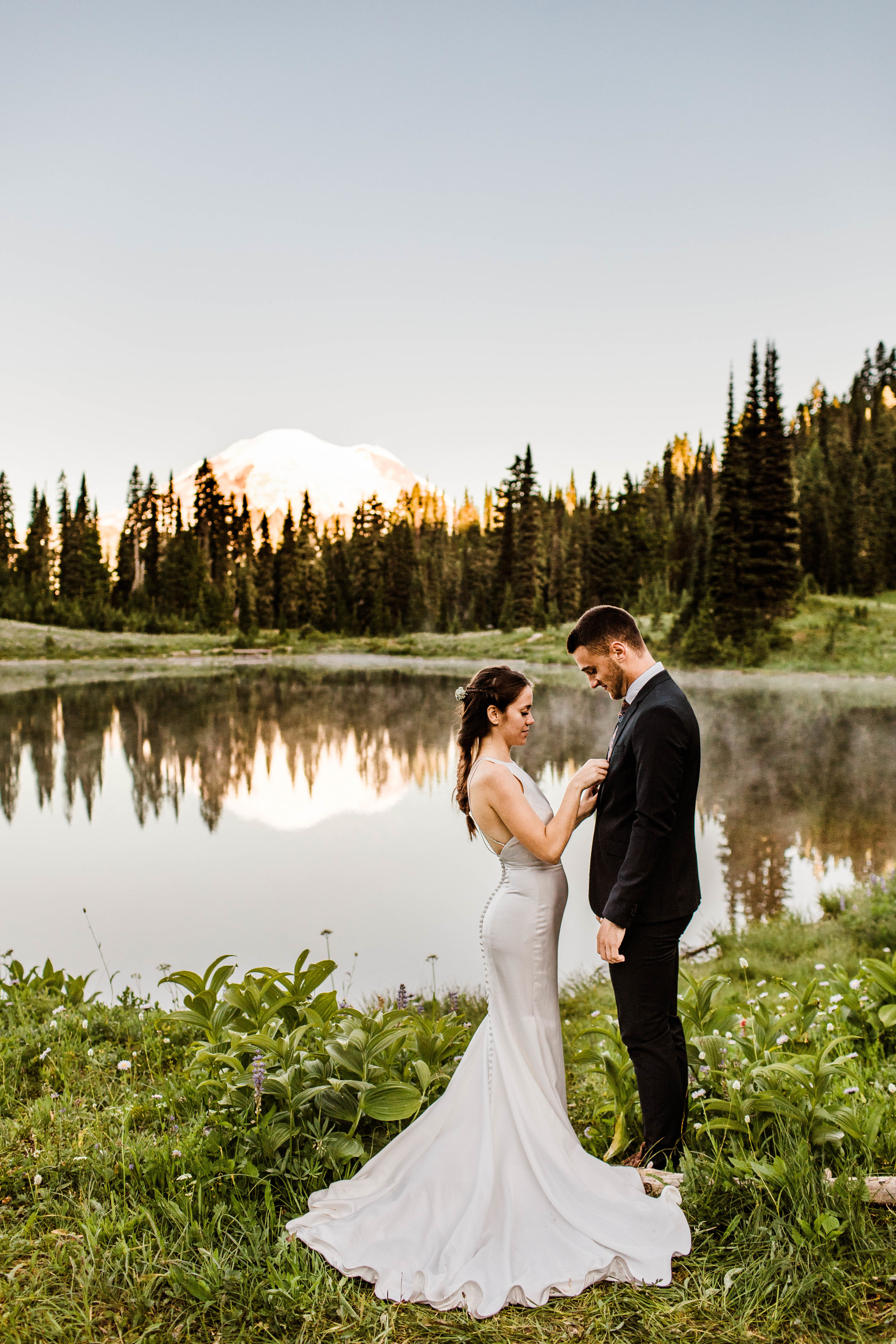 eloping couple standing by an alpine lake during their Mount Rainier National Park elopement | Washington state adventure wedding photographers