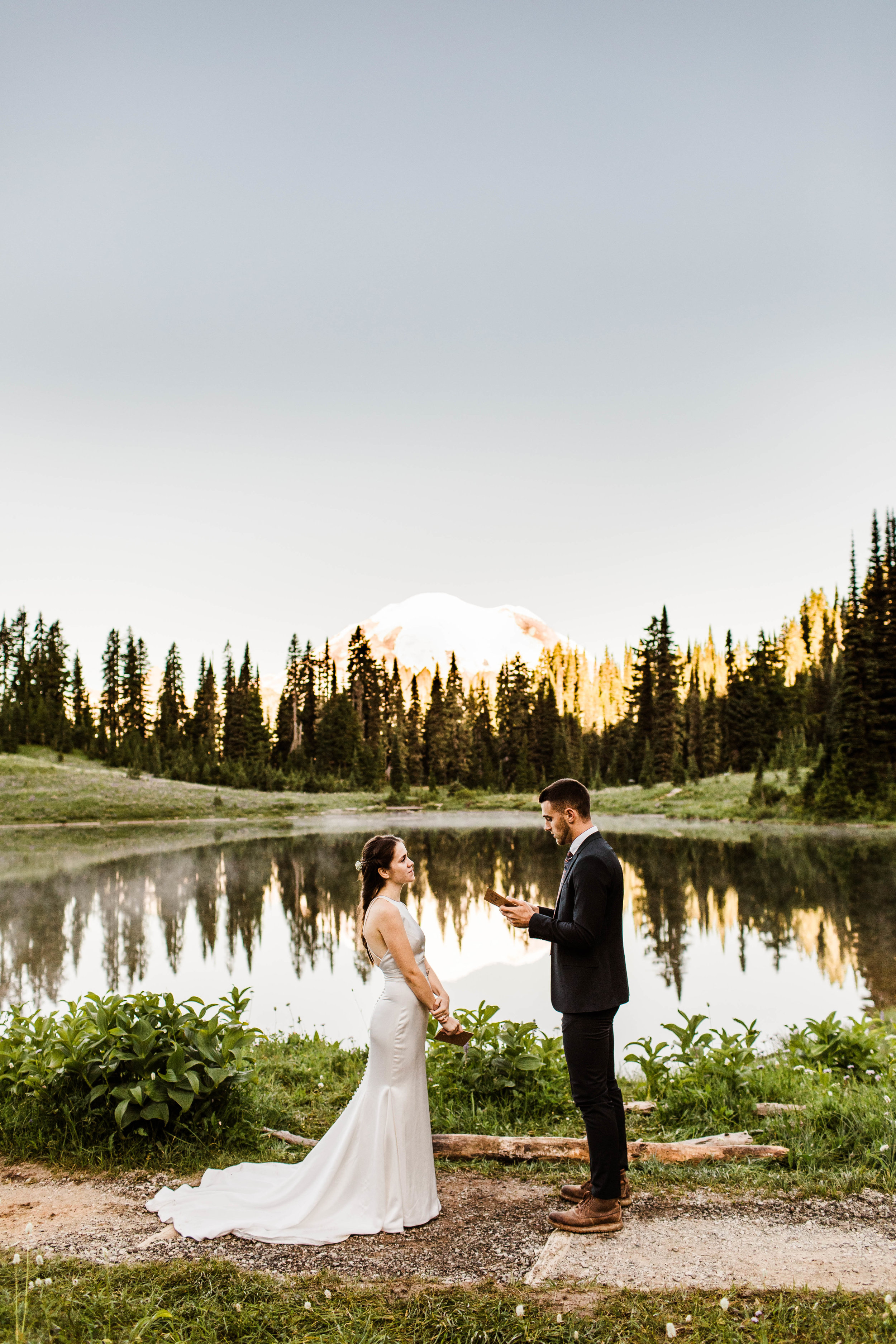 groom reading vows during Mount Rainier elopement ceremony in the mountains | Washington national park adventure wedding photographers