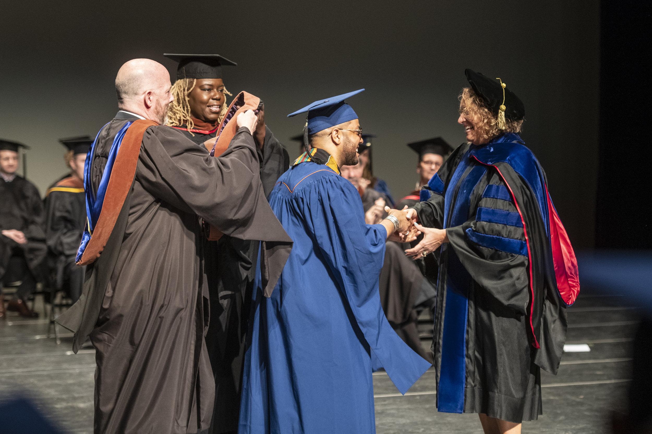 Professors Robert G. Anderson and Lisa Gaye Dixon hood Raffeal.  Photo by Darell Hoeman