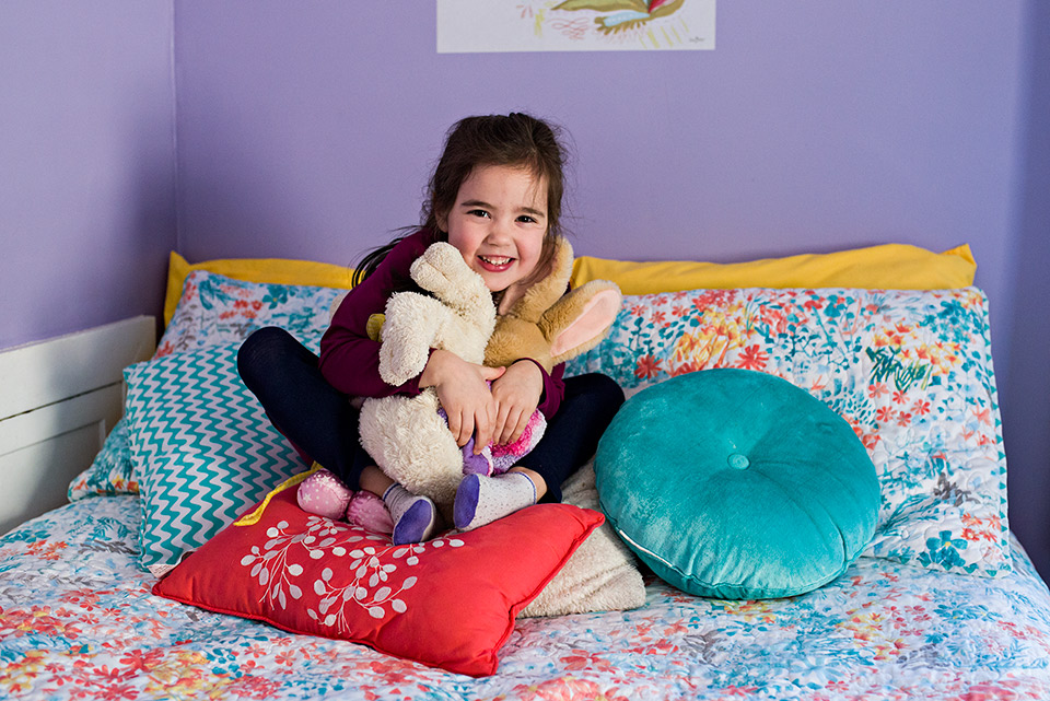 girl sitting on bed hugging stuffed animals west hartford connecticut family documentary photography