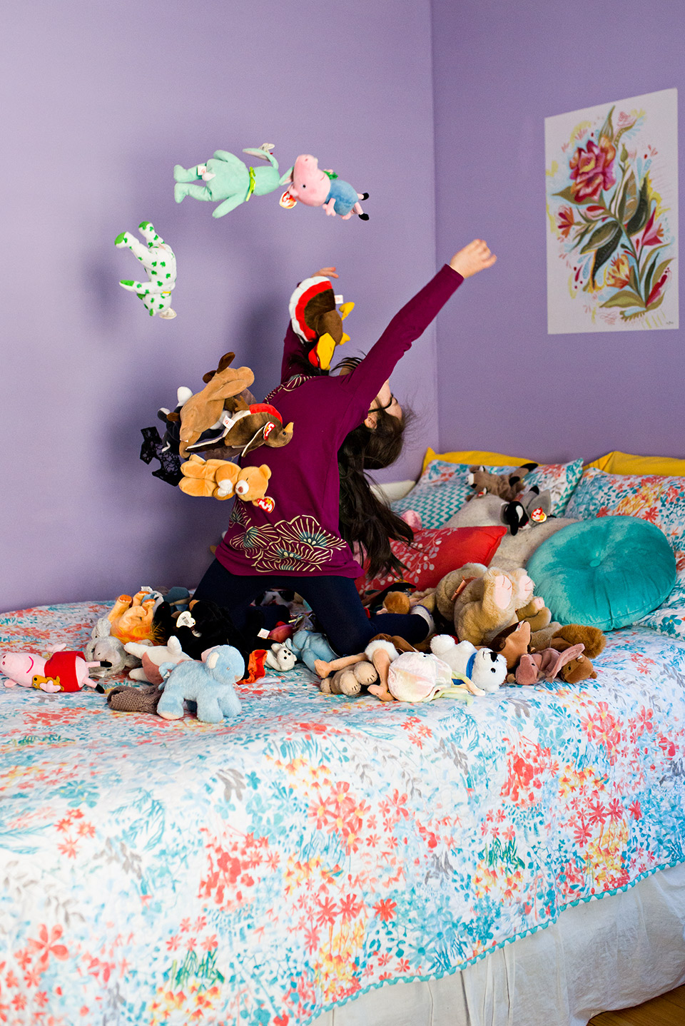girl throwing stuffed animals in the air on her bed west hartford ct family documentary photography