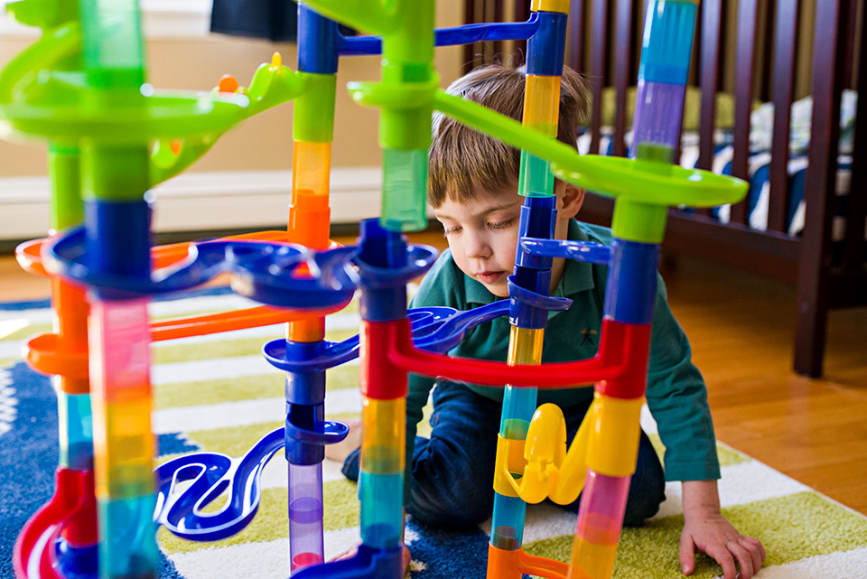 boy playing with marble run in bedroom on green carpet west hartford connecticut family documentary photography