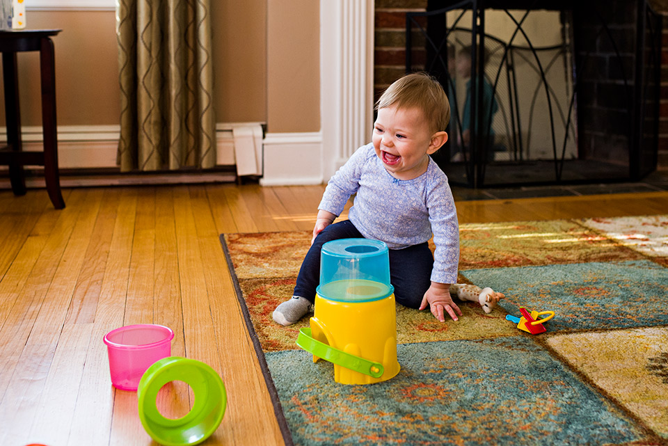 baby girl laughing after knocking down stacking cup toy west hartford ct family documentary photography