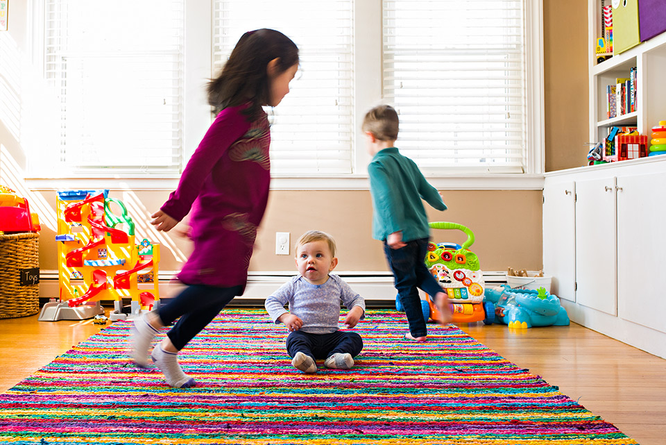 brother and sister running in circles around baby sister in playroom west hartford connecticut family documentary photography
