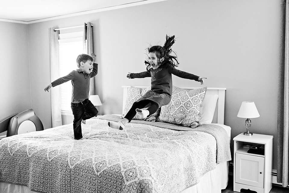brother and sister jumping on mom and dads bed west hartford ct documentary family photography