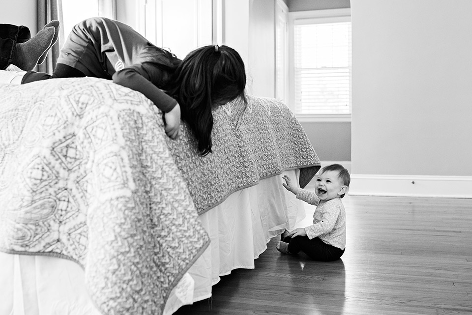 big sister playing peek a boo with baby sister west hartford ct family documentary photography