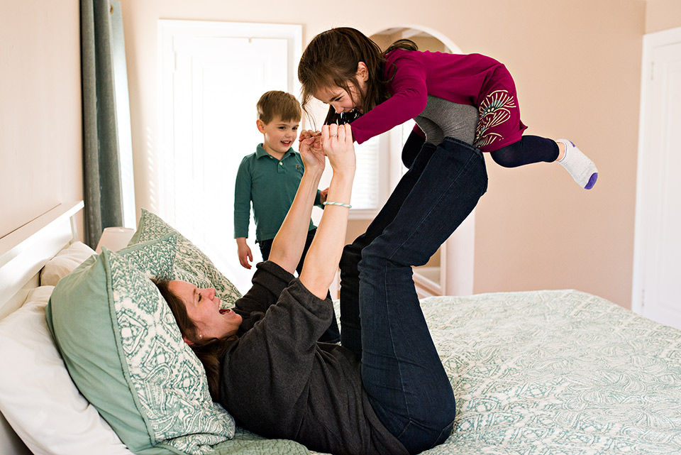 mom playing airplane with daughter on her feet up in the air west hartford connecticut family documentary photography