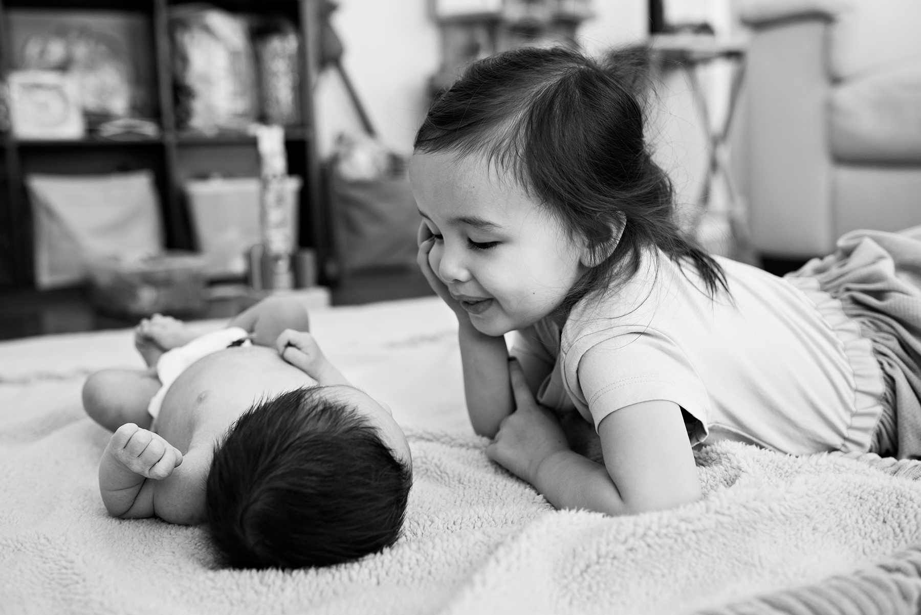 big sister smiling at newborn baby brother at middletown connecticut lifestyle newborn photography