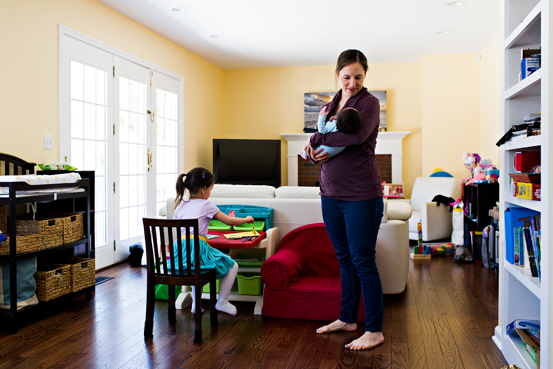 mom holding baby in living room while daughter colors at desk lifestyle newborn photography middletown connecticut