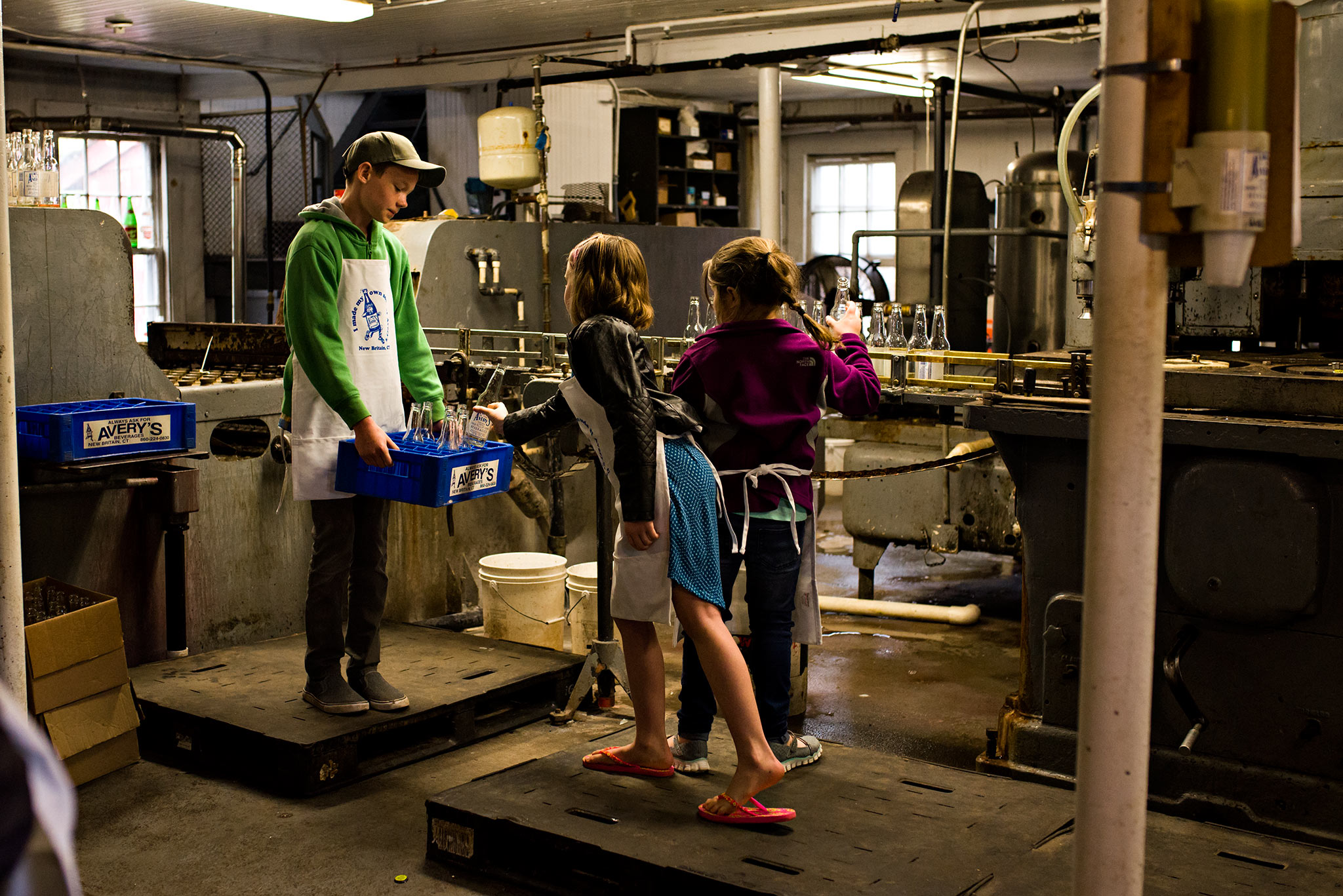 children filling carton with clean soda bottles averys soda connecticut documentary photographer