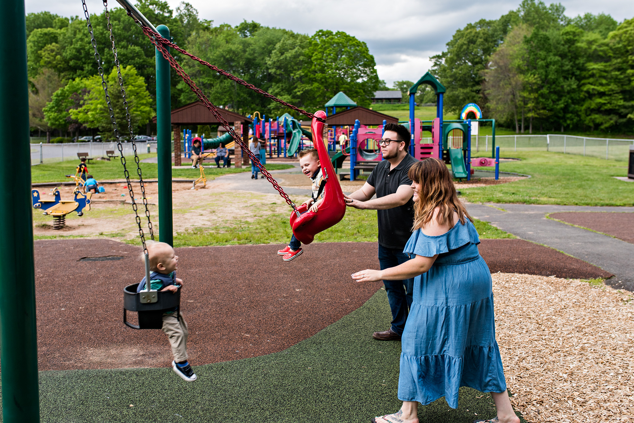 parents pushing children on swings at the park plainville ct family photography