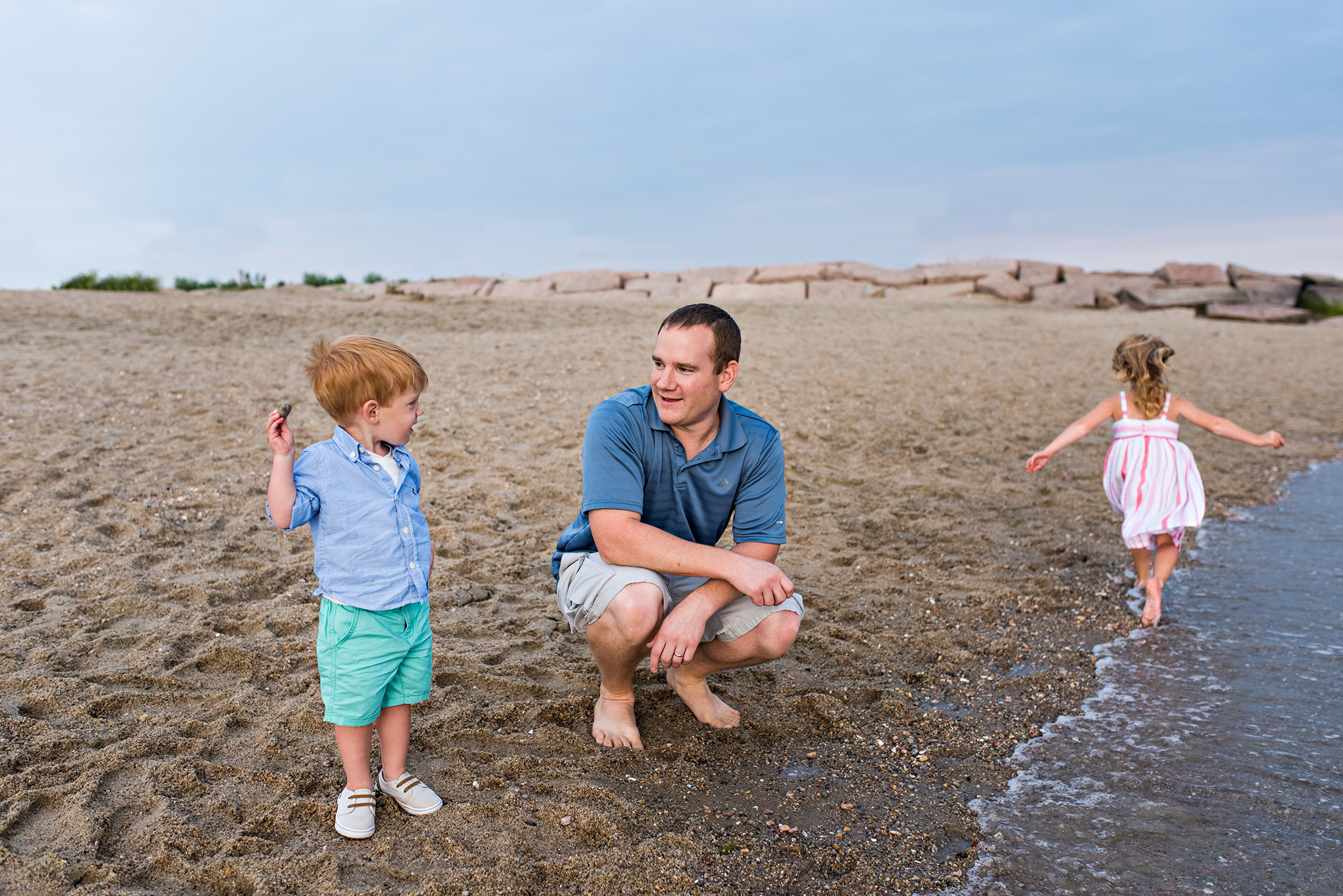 child throwing rock into the water with dad connecticut lifestyle family photographer