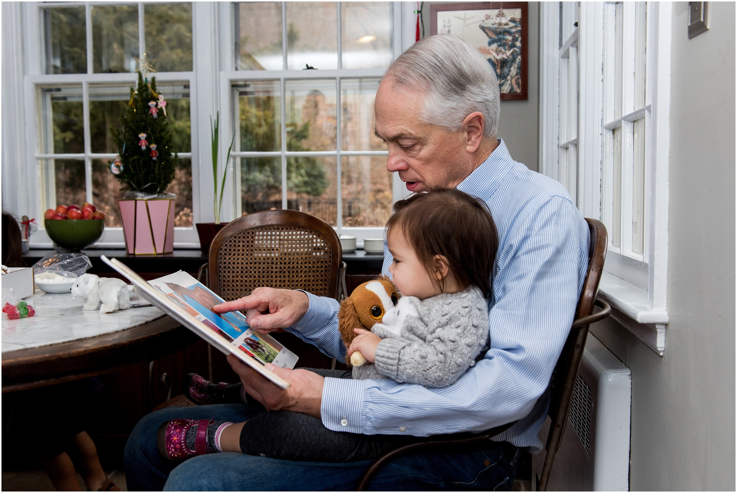 grandpa reading book to granddaughter during ct extended family photography