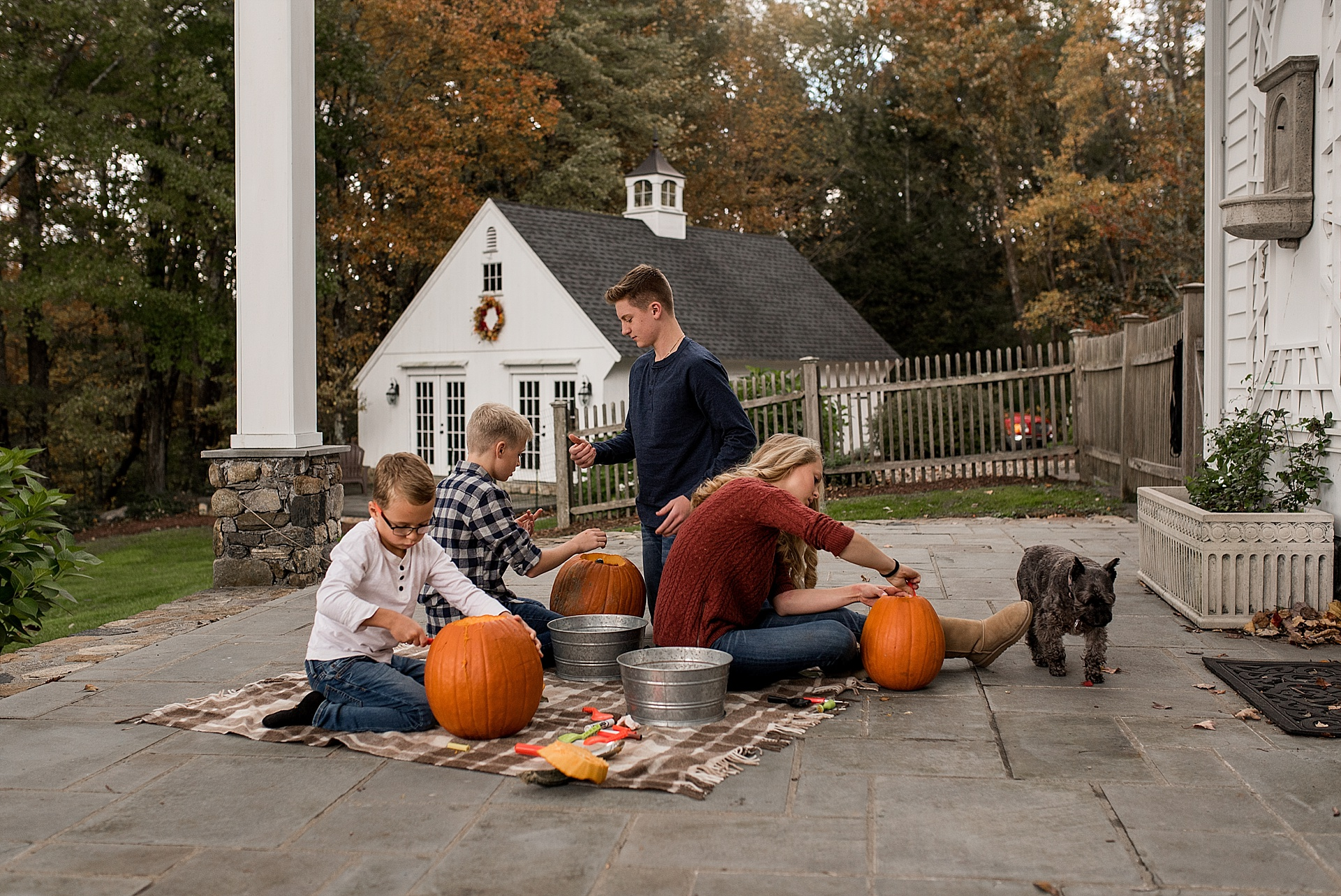 connecticut children carving pumpkins on their back pourch. litchfield county family photographer.