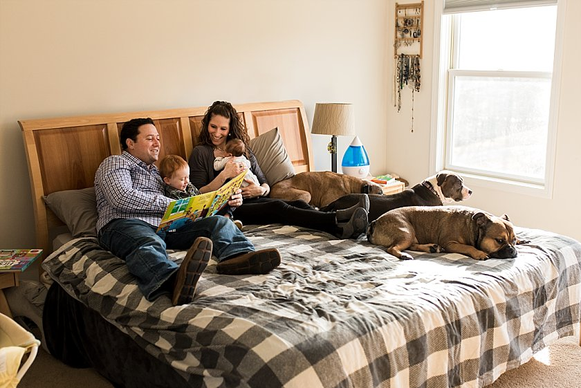 Dad reading books to son in bed during at home newborn photography session in Connecticut.