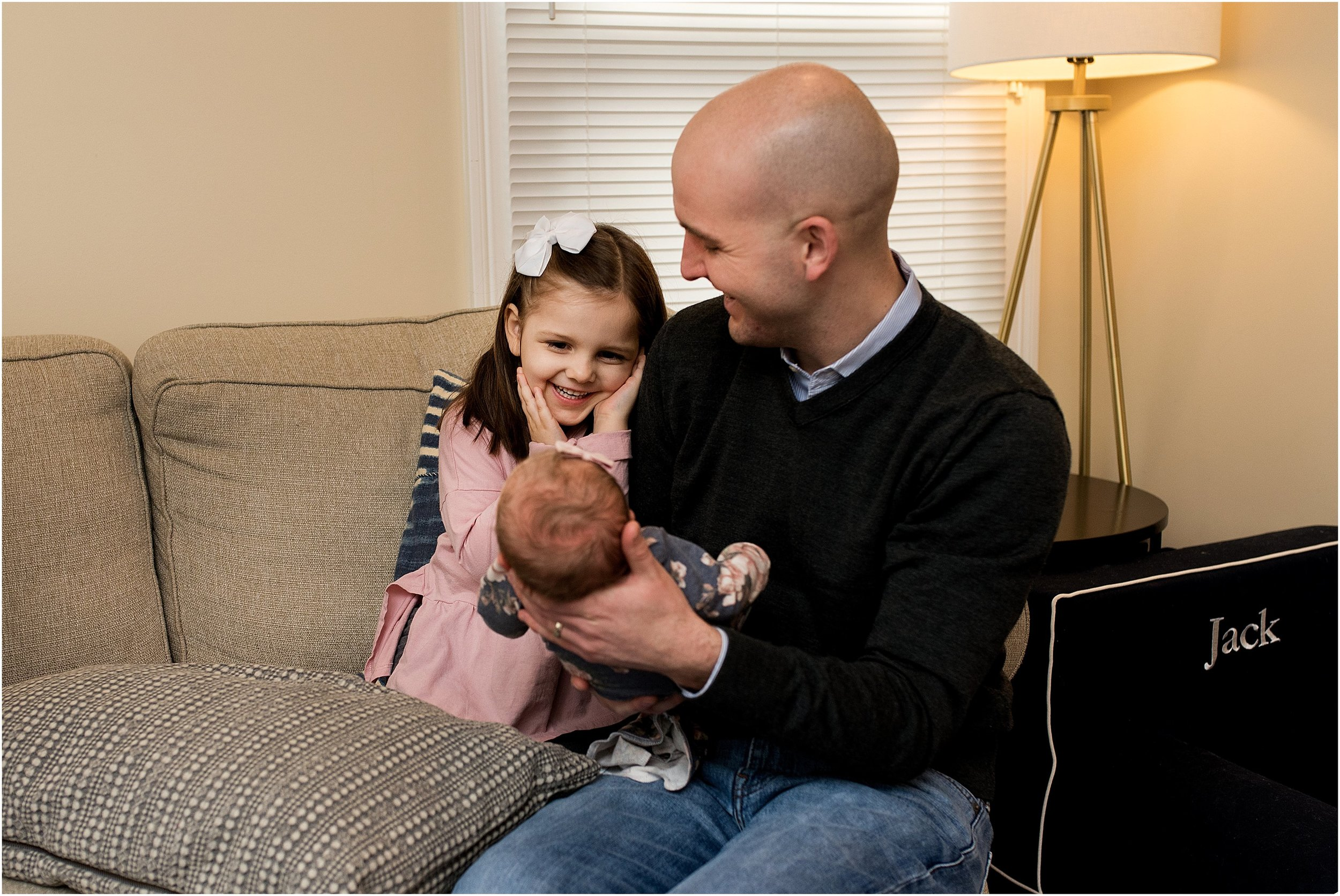 Dad holding baby daughter during Connecticut newborn photography session.