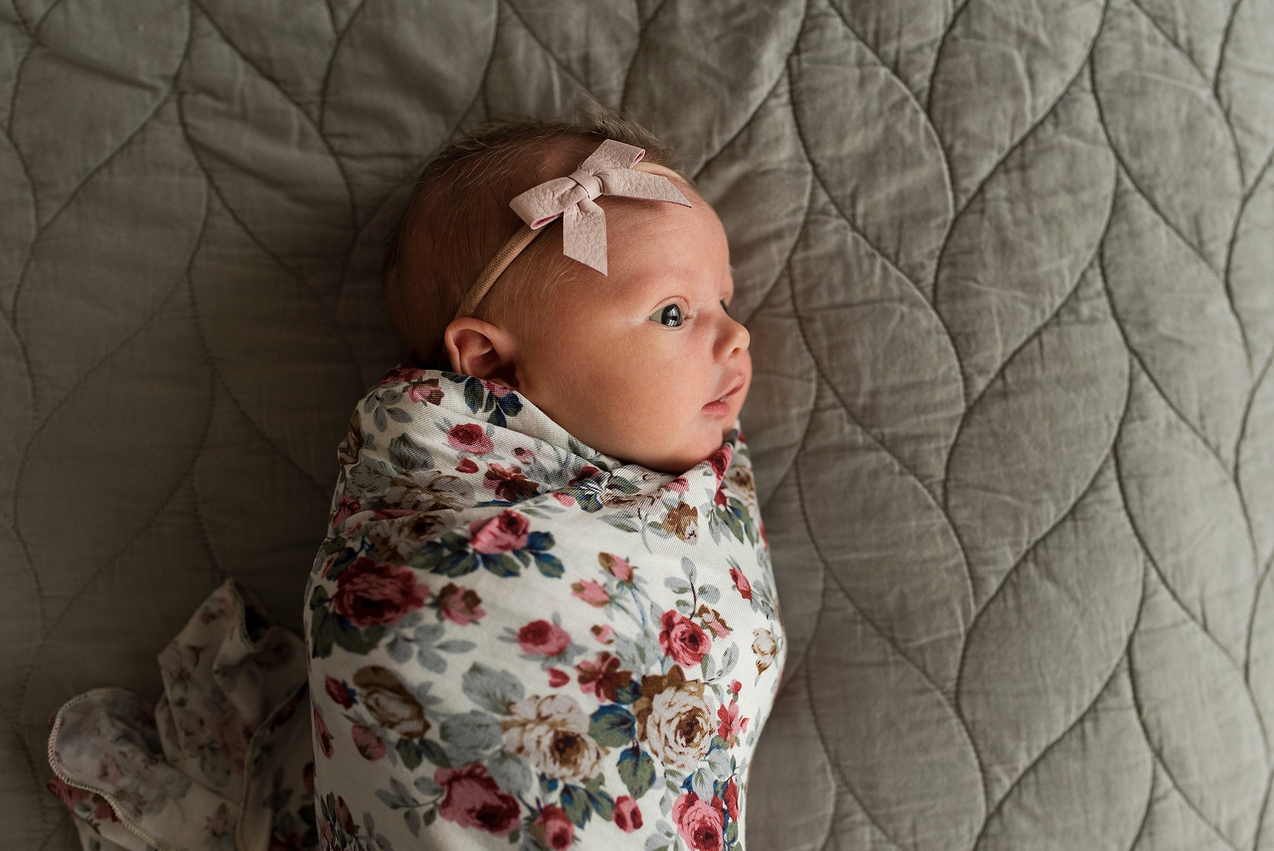 CT newborn baby girl in floral swaddle and pink headband during photography session.