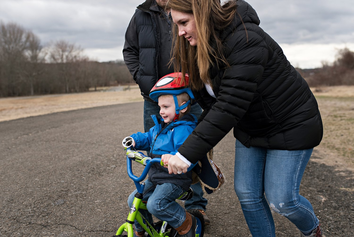 Mom helping toddler boy ride his bike during connecticut professional family photos