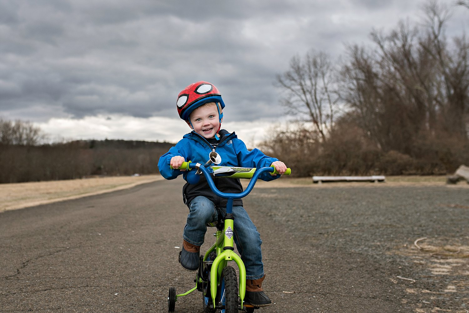 toddler boy riding bike during professional family photos in ct