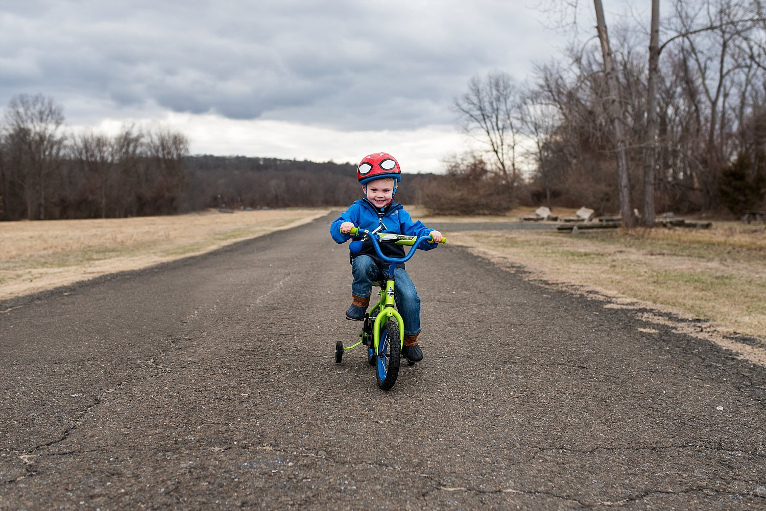 toddler boy in blue jacket riding green bike during ct professional family photos