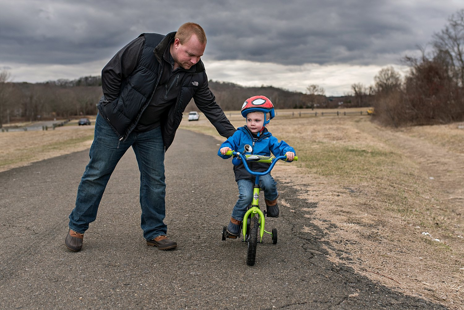 Dad helping son ride bike during ct professional family photos