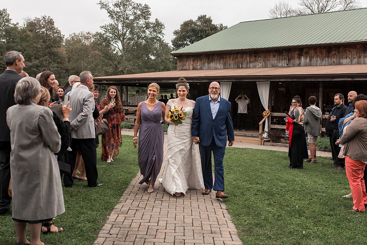 mom and dad walking their daughter down the isle at wood acres farm