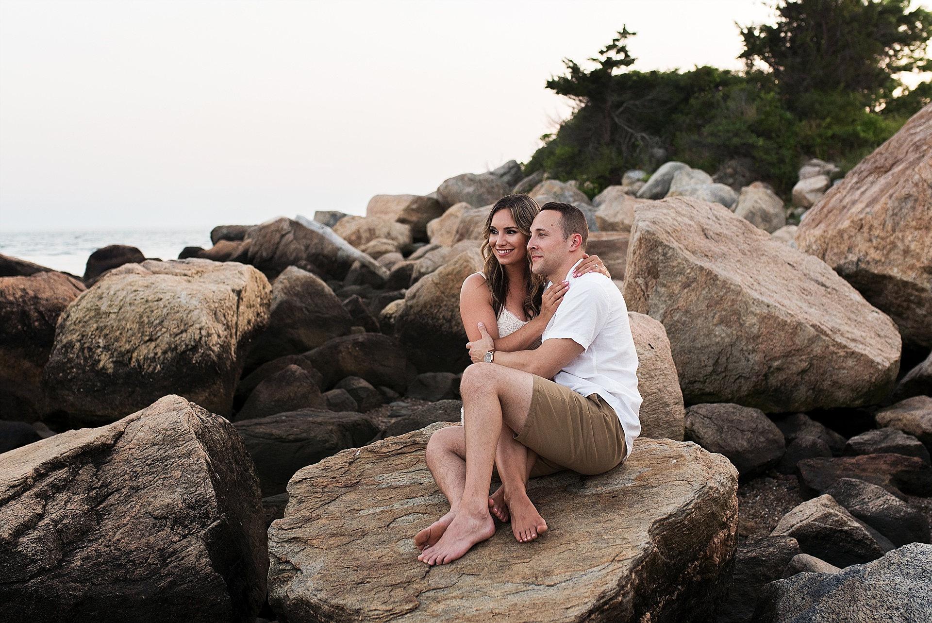 engaged couple sitting on rocks in madison, ct