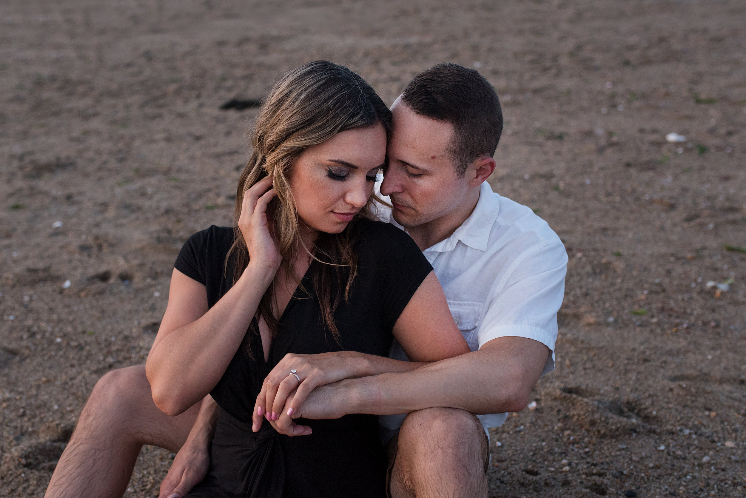 romantic couple sitting on the beach in connecticut during their photo session